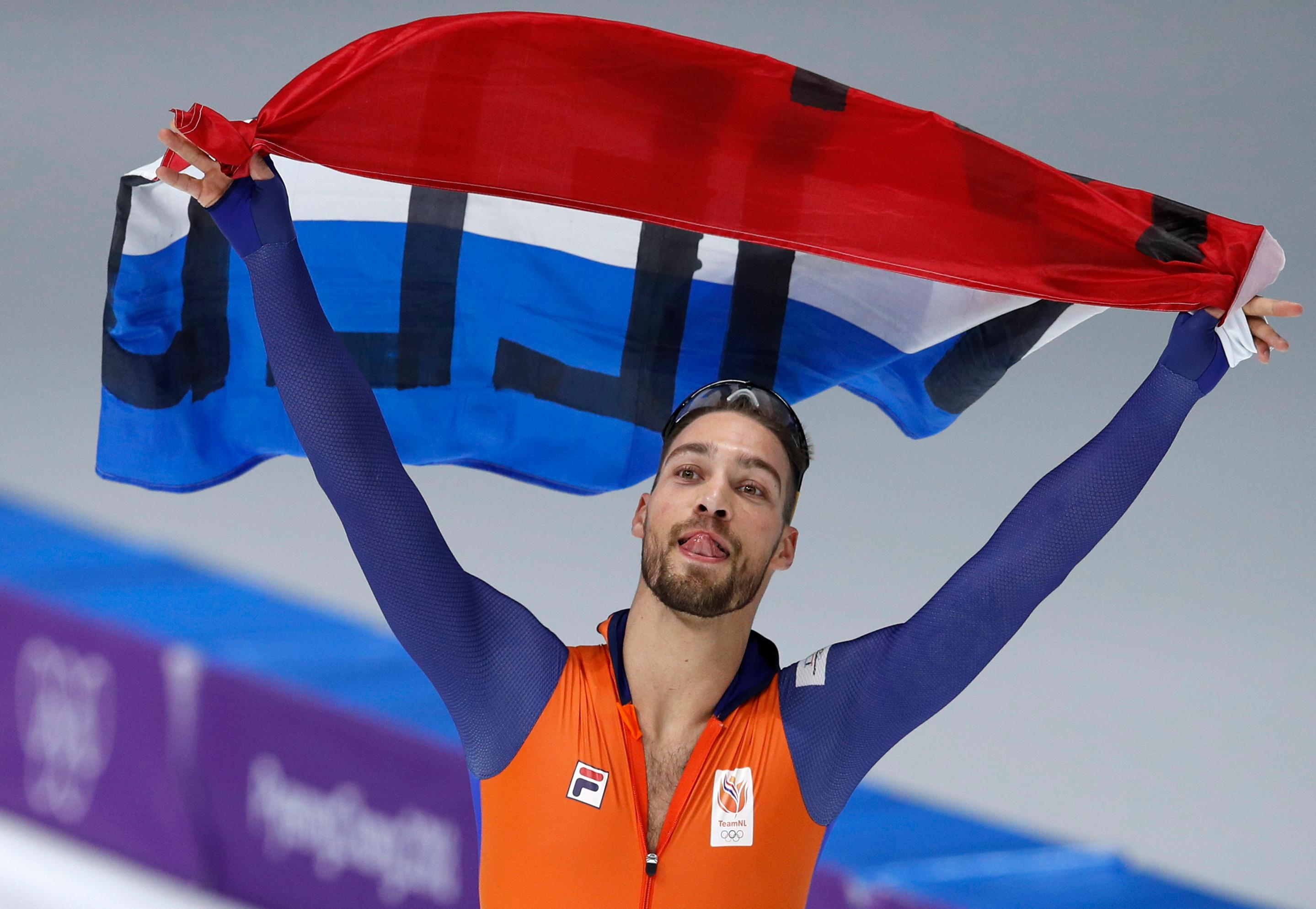 Gold medalist Kjeld Nuis of The Netherlands celebrates with the national flag after the men's 1,000 meters speedskating race at the Gangneung Oval at the 2018 Winter Olympics in Gangneung, South Korea, Friday, Feb. 23, 2018. (AP Photo/Vadim Ghirda)