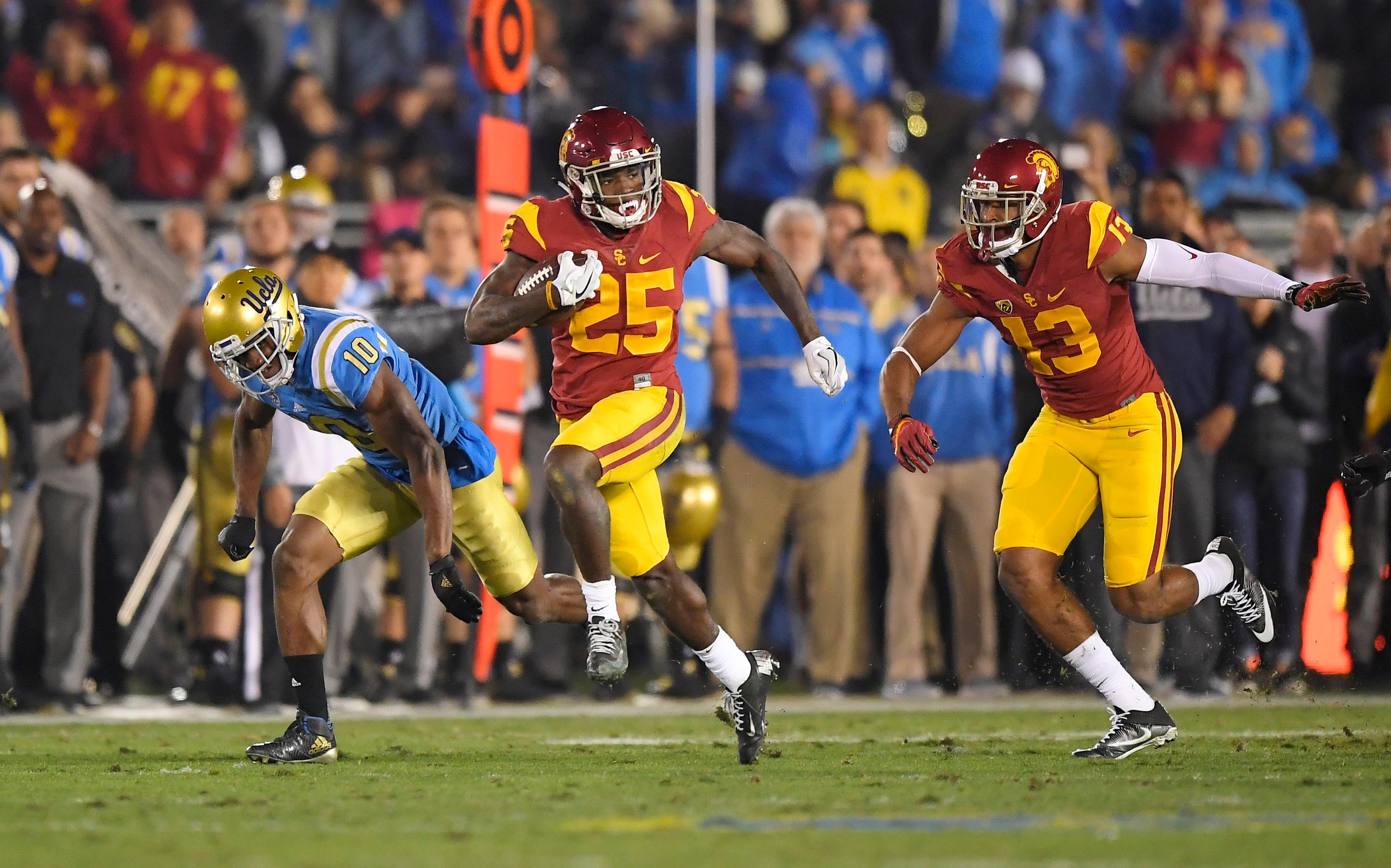 FILE - In this Nov. 19, 2016, file photo, Southern California running back Ronald Jones II, center, runs 60 yards for a touchdown as UCLA defensive back Fabian Moreau, left, runs behind along with wide receiver De'Quan Hampton during the first half of an NCAA college football game, in Pasadena, Calif. Jones was selected to the 2017 AP All-Conference Pac-12 team announced Thursday, Dec. 7, 2017. (AP Photo/Mark J. Terrill, File)