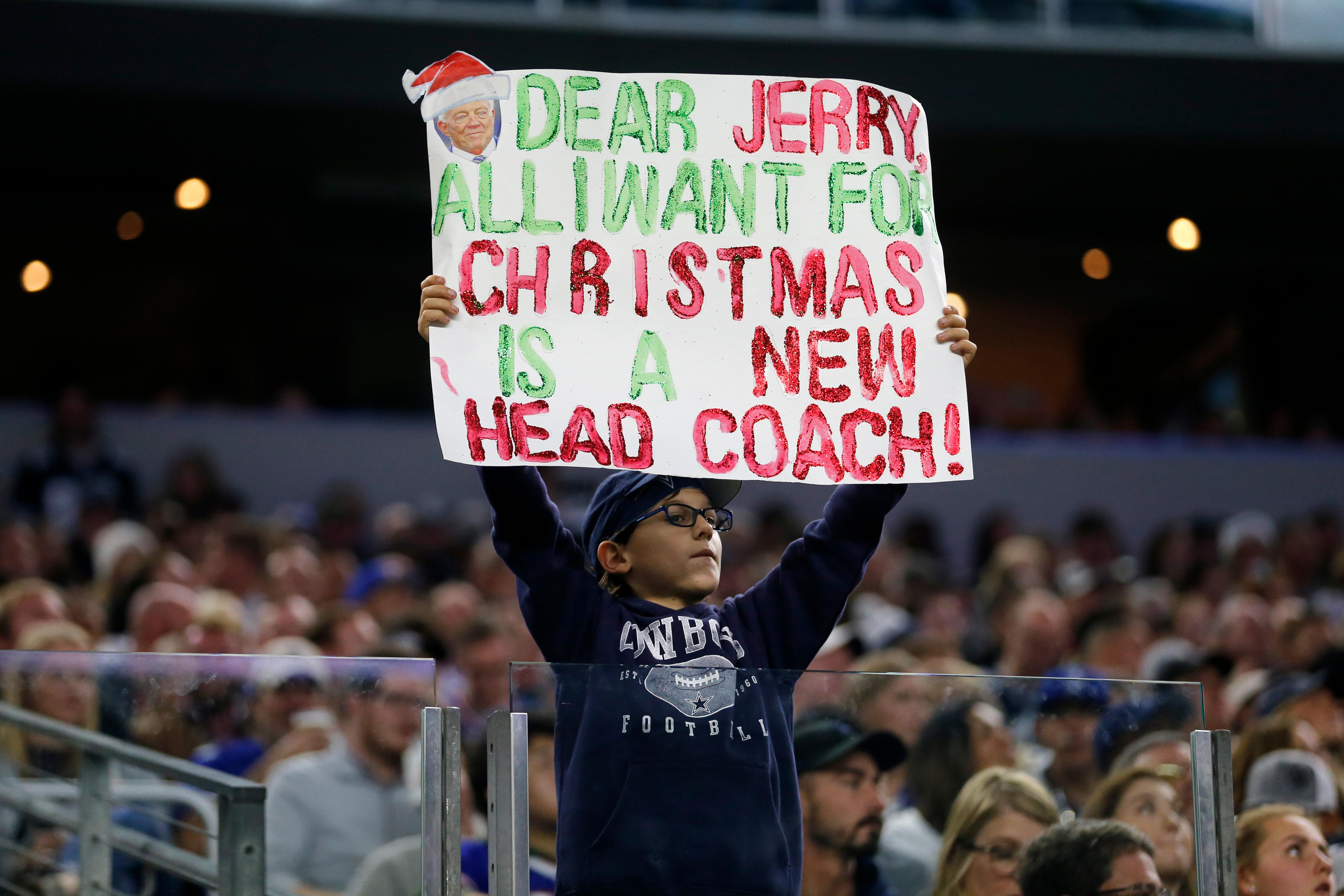 A young fan holds up a sign asking Dallas Cowboys team owner Jerry Jones for a new head coach in the first half of an NFL football game against the Buffalo Bills in Arlington, Texas, Thursday, Nov. 28, 2019. (AP Photo/Michael Ainsworth)