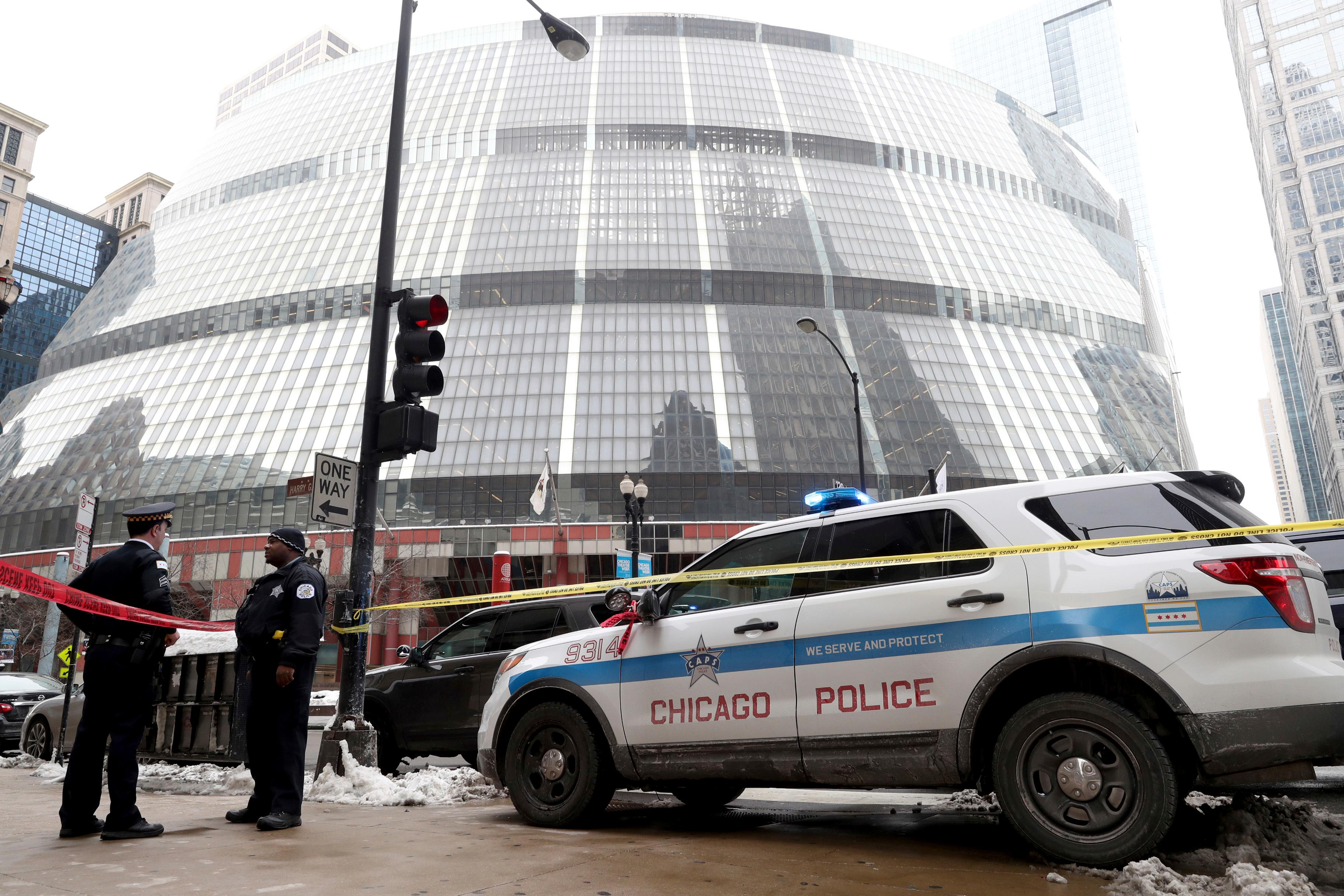 Police guard the crime scene after an off-duty Chicago police officer was shot at the James R. Thompson Center, in Chicago, Tuesday, Feb. 13, 2018. Spokesman Anthony Guglielmi says the off-duty officer was shot around 2 p.m. Tuesday at the James R. Thompson Center. Guglielmi says the preliminary information is that the shooting happened