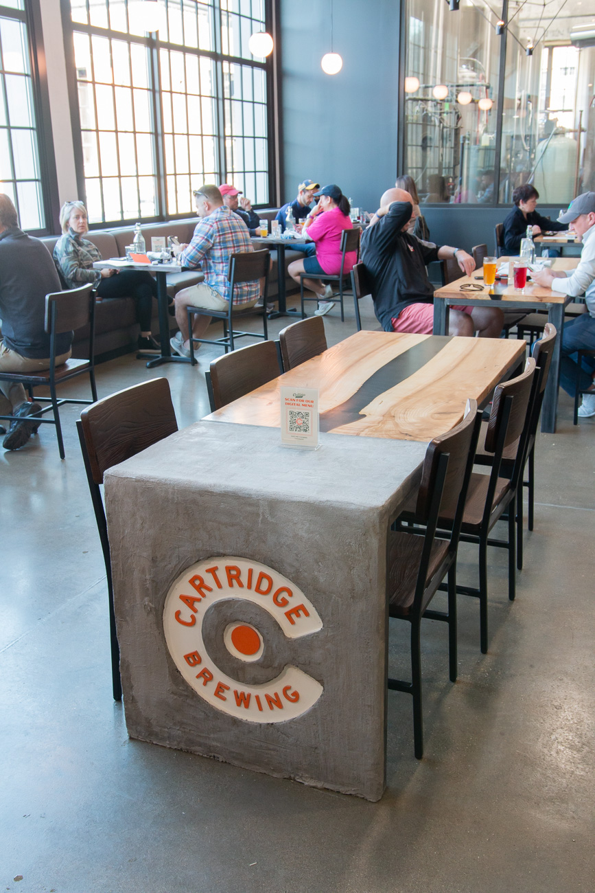 "Custom wood and concrete river tables were created to showcase their Cartridge ""C"" logo and were made by an old army buddy of Kyle's. / Image: Elizabeth A. Lowry{ }// Published: 11.25.20"