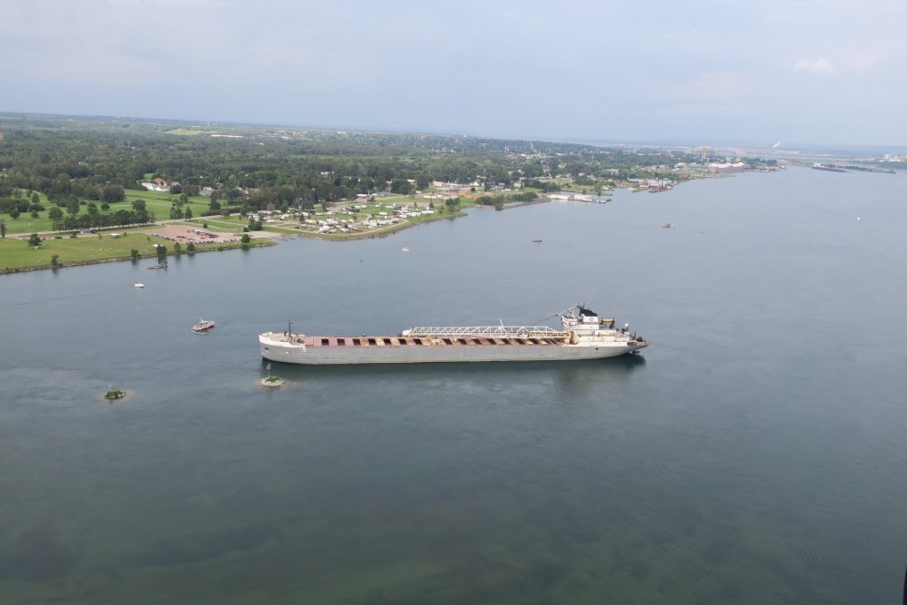 The 629-foot cargo vessel Calumet sits hard aground in the St. Mary's River southeast of Sault Ste. Marie, Michigan, while a Coast Guard response boat - medium encircles the vessel, August 10, 2017. The vessel was heading to its next port of call in Brevort, Michigan when it ran aground. (Photo: U.S. Coast Guard)