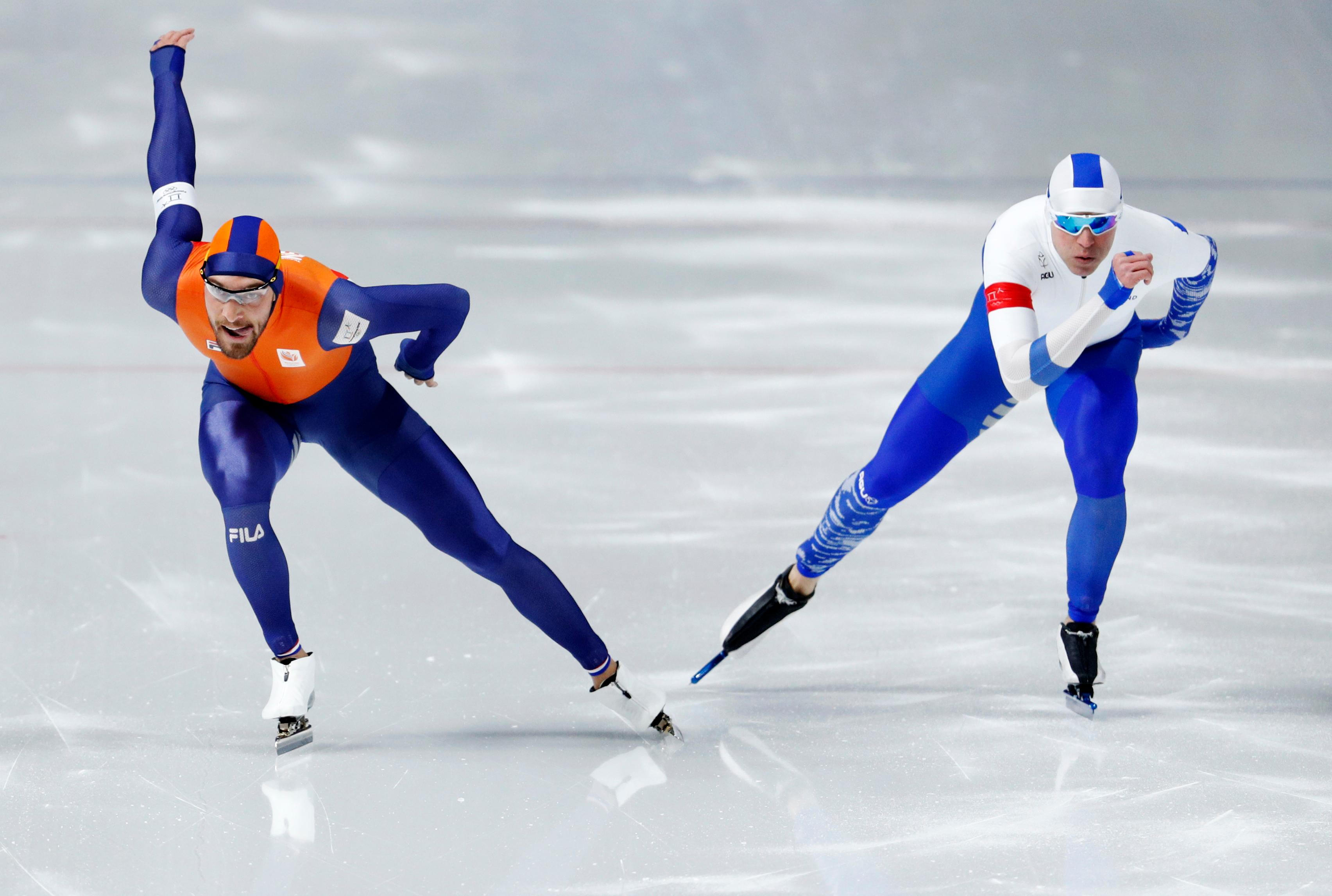 Gold medalist Kjeld Nuis of The Netherlands crosses over to the inside lane where Mika Poutala of Finland holds back and makes way to let Nuis through and make sure he does not ruin his gold medal race during the men's 1,000 meters speedskating race at the Gangneung Oval at the 2018 Winter Olympics in Gangneung, South Korea, Friday, Feb. 23, 2018. (AP Photo/John Locher)