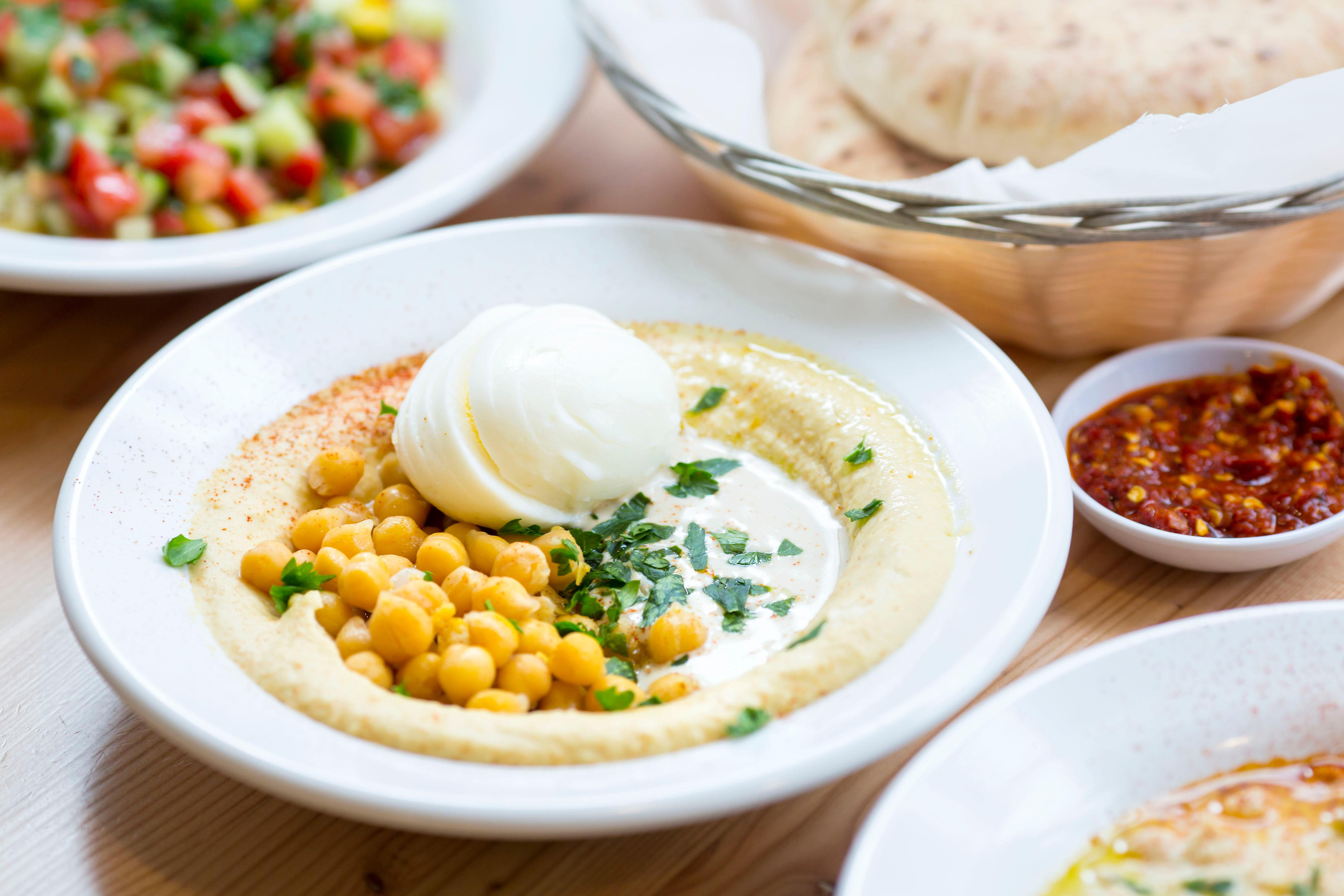 "The Classic - served with tender boiled chickpeas, citrusy nutty tahina, and topped with a side order of egg. Aviv Hummus Bar is a 100% Israeli hummus bar, straight from the streets of Tel Aviv. And now, it's on Capitol Hill! Fun fact: Hummus literally means chickpeas. And while the west has kind of appropriated hummus and made it its own thing, traditional hummus isn't a sauce, or a dip, it's supposed to be a eaten as a meal consisting of smashed chickpeas, ""tahina"" and lemon. Enter Aviv Hummus Bar - trying to educate through this food. The Hummus Bar is located on 107 15th Ave E, Seattle. (Image: Sy Bean / Seattle Refined)"