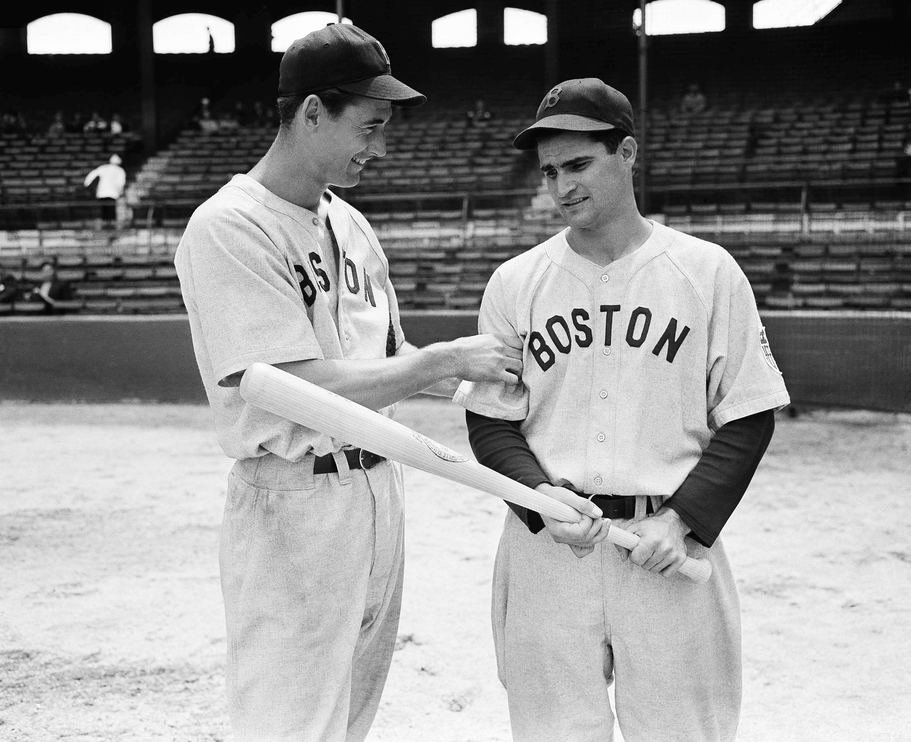 "FILE - In this May 14, 1942, file photo, Boston Red Sox left fielder Ted Williams, left, tests the arm of Red Sox second baseman Bobby Doerr before their game against the White Sox, in Chicago. Doerr, a Hall of Fame second baseman who was dubbed the ""silent captain"" by longtime Red Sox teammate and life-long friend Ted Williams, has died. He was 99. (AP Photo/File)"