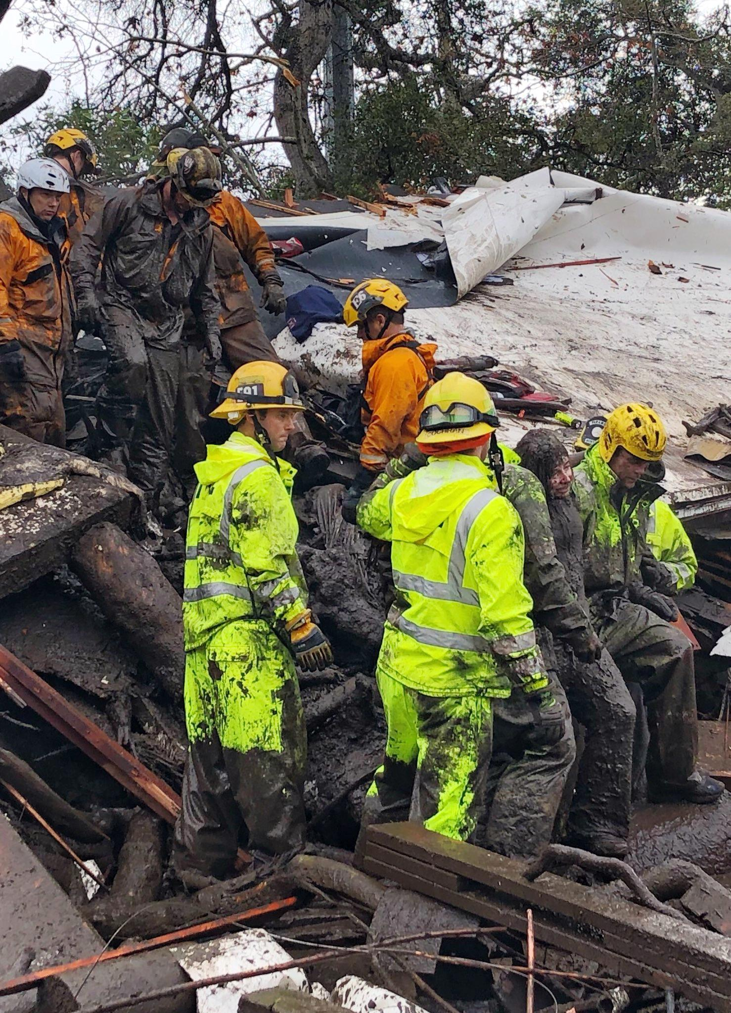 In this photo provided by Santa Barbara County Fire Department, firefighters successfully rescue a 14-year-old girl, right, after she was trapped for hours inside a destroyed home in Montecito, Calif., Tuesday, Jan. 9, 2018. Dozens of homes were swept away or heavily damaged and several people were killed Tuesday as downpours sent mud and boulders roaring down hills stripped of vegetation by a gigantic wildfire that raged in Southern California last month. (Mike Eliason/Santa Barbara County Fire Department via AP)