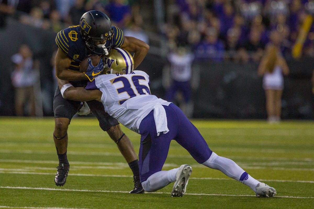 Oregon Ducks running back Tony Brooks-James (#20) is brought down by Washington Huskies linebacker Azeem Victor (#36). The Oregon Ducks fell to the Washington Huskies 70-21. Photo by Dillon Vibes