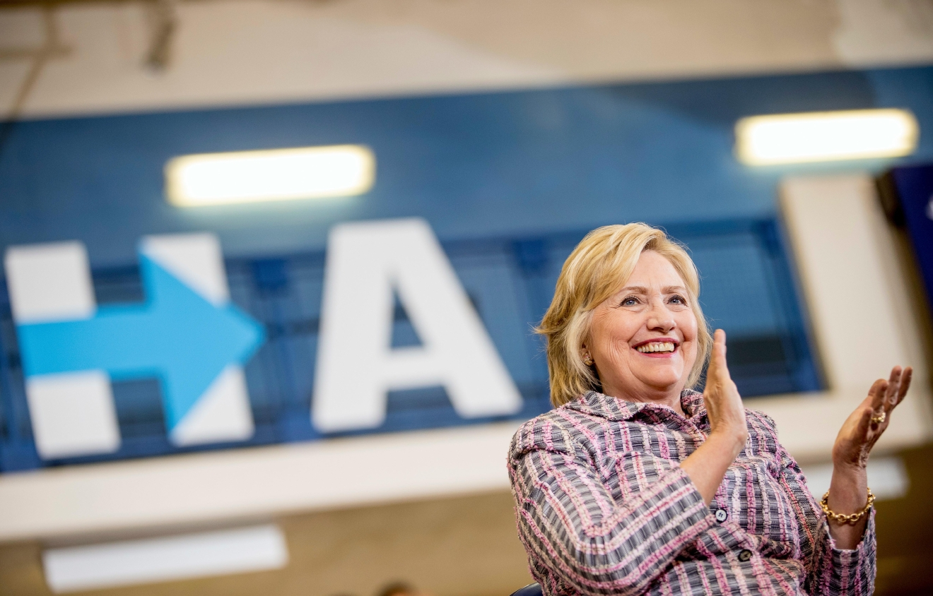 Democratic presidential candidate Hillary Clinton applauds as she sits on stage at a rally at Omaha North High Magnet School in Omaha, Neb., Monday, Aug. 1, 2016. (AP Photo/Andrew Harnik)