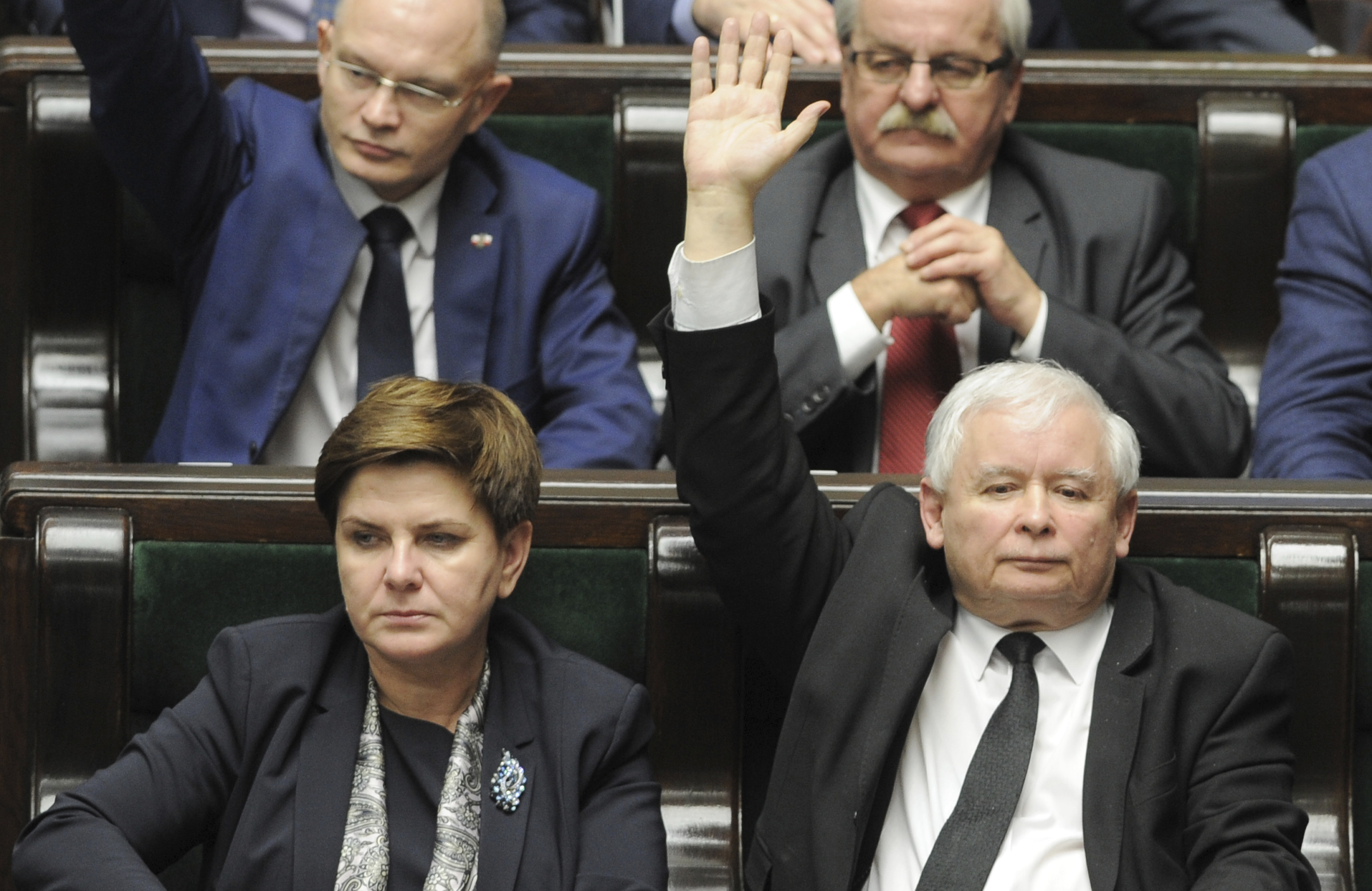 FILE - In this Dec. 22, 2015 file photo the leader of the ruling Law and Justice party, Jaroslaw Kaczynski, right, raises his hand during one of the votes passing a new law on the constitutional court, as Prime Minister Beata Szydlo, left, looks on, in the parliament in Warsaw, Poland.  Prime Minister Szydlo sent a tweet early Tuesday, Dec. 5, 2017 that seems to read like a farewell, amid rumors in Warsaw that she might be replaced by Finance Minister Mateusz Morawiecki.  (AP Photo/Alik Keplicz, file)