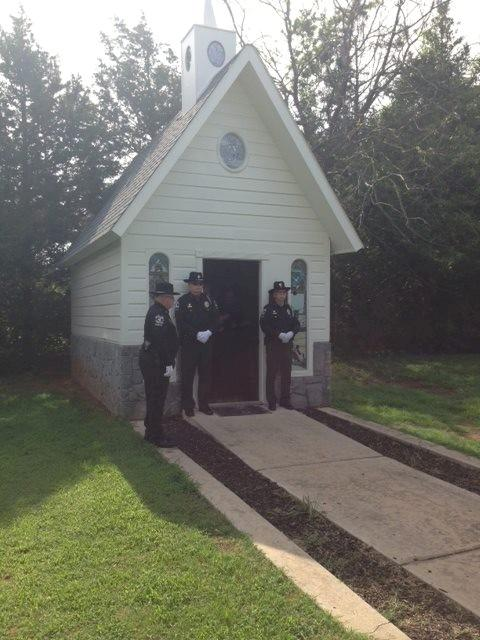 Officers wait outside the chapel for Eron's casket at Precious Pets Cemetery