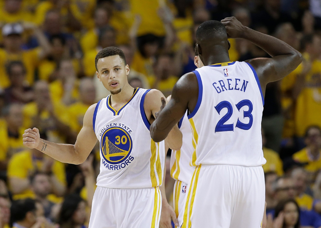 Golden State Warriors guard Stephen Curry (30) and forward Draymond Green (23) react after scoring against the Oklahoma City Thunder during the first half of Game 2 of the NBA basketball Western Conference finals in Oakland, Calif., Wednesday, May 18, 2016. (AP Photo/Marcio Jose Sanchez)