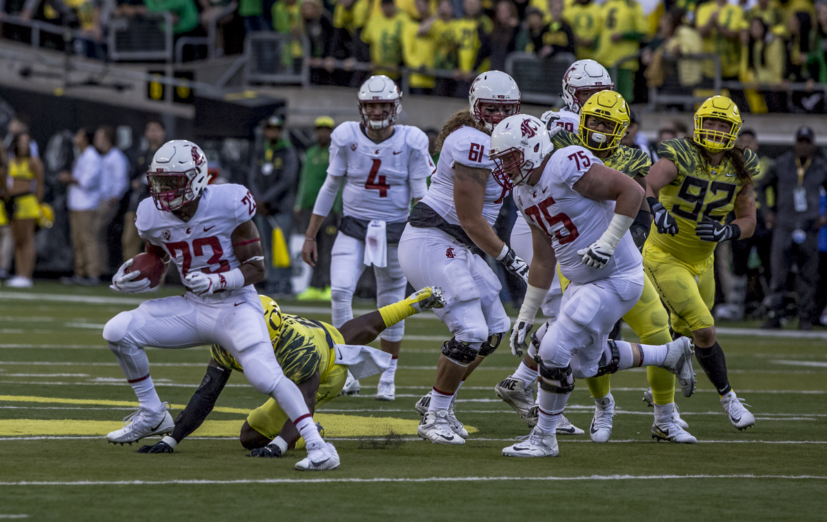 Washington State running back Gerard Wicks pulls away from the Oregon defense. The Oregon Ducks trail the Washington State Cougars 10 to 13 at the end of the first half. Photo by Ben Lonergan, Oregon News Lab