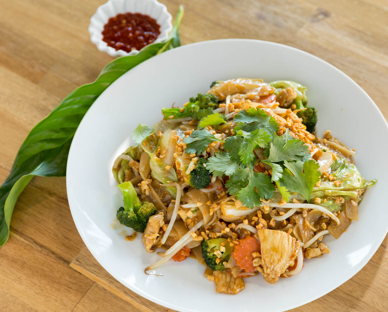 Kua Gai noodle: wide rice noodle in house dark sauce & light sesame oil with chicken, egg, white onion, broccoli, carrot, lettuce, bean sprouts, and topped with cilantro and fried garlic{ }/ Image: Marlene Rounds // Published: 1.17.19