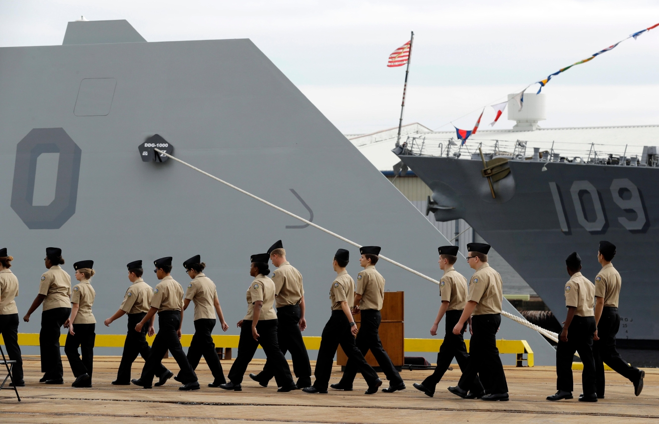 In this Oct. 13, 2016 photo, members of the Navy Junior Reserve Officers Training Corps walk past the bow of the future USS Zumwalt, the U.S. Navy's newest guided-missile destroyer, in Baltimore.  The destroyer's commissioning ceremony is set for Oct. 15 in Baltimore, and its home port will be in San Diego. (AP Photo/Patrick Semansky)