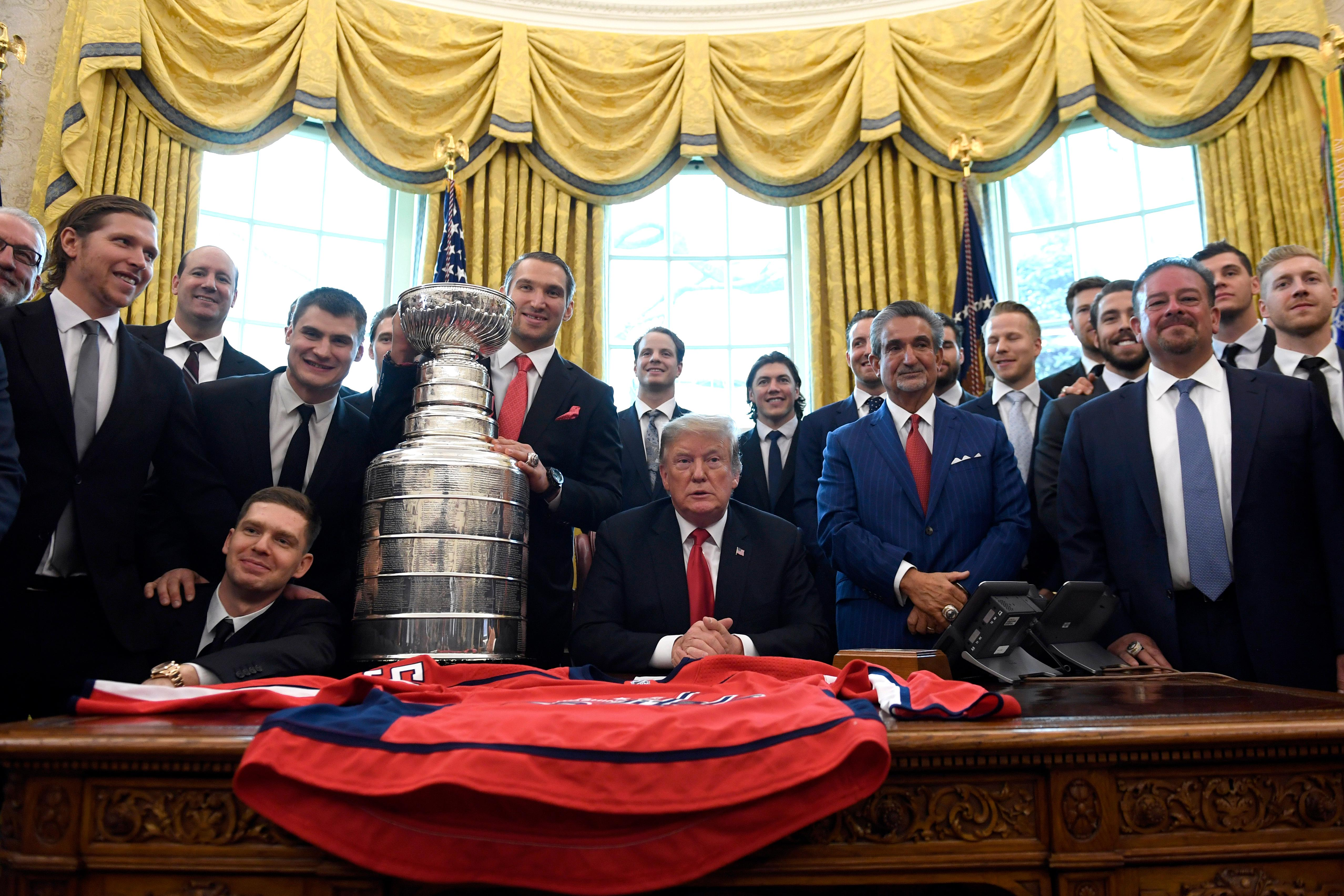 President Donald Trump, center, poses for a photo as he hosts the 2018 Stanley Cup Champion Washington Capitals hockey team in the Oval Office of the White House in Washington, Monday, March 25, 2019. (AP Photo/Susan Walsh)