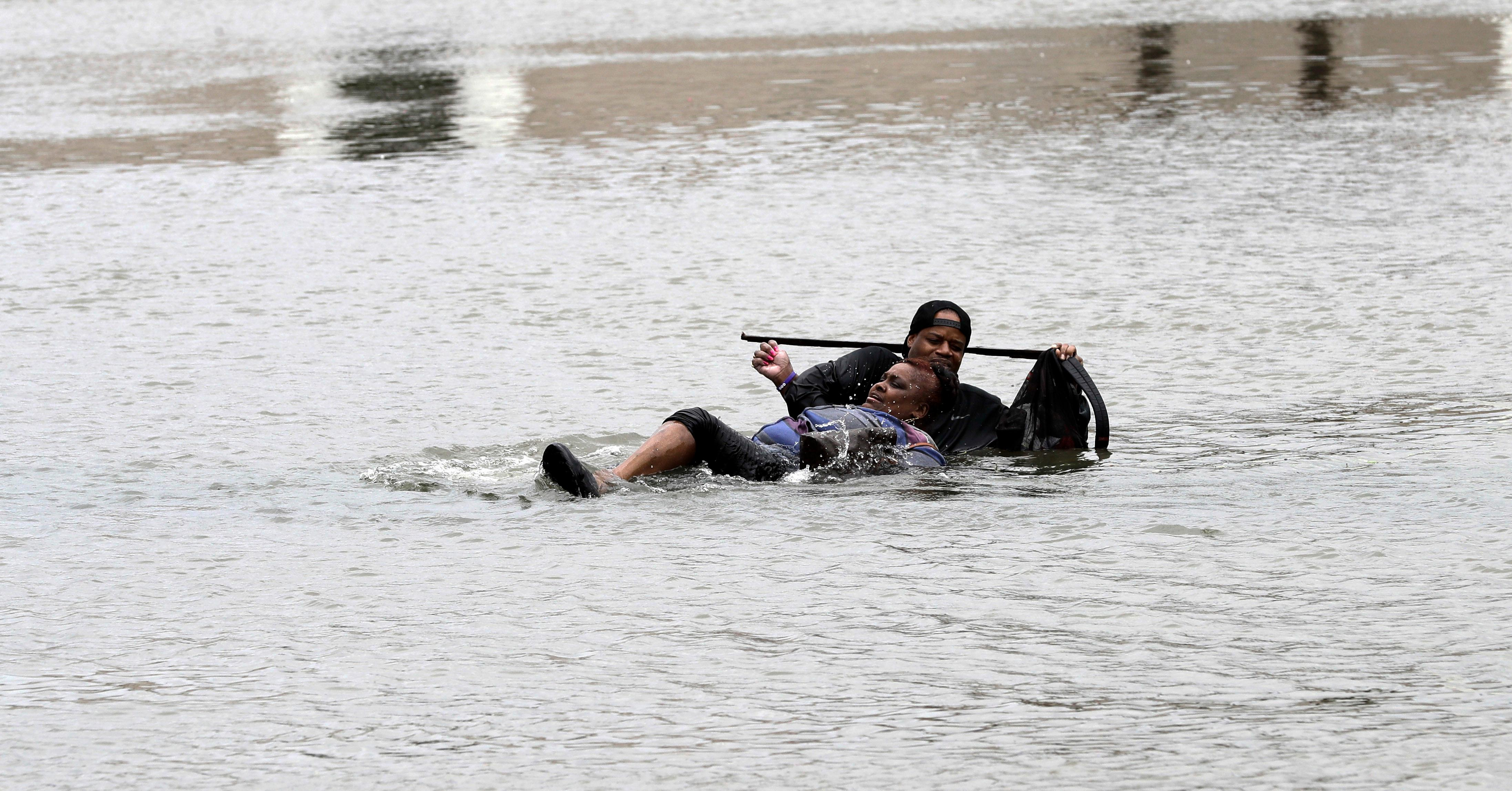 A man helps a woman in floodwaters from Tropical Storm Harvey Sunday, Aug. 27, 2017, in Houston, Texas. The remnants of Hurricane Harvey sent devastating floods pouring into Houston Sunday as rising water chased thousands of people to rooftops or higher ground. (AP Photo/David J. Phillip)