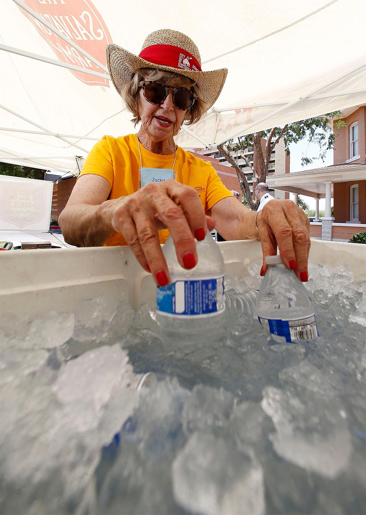Salvation Army volunteer Jackie Rifkin checks to see if the new bottles of water in a cooler are getting cold enough to hand out to people as they try to keep hydrated and stay cool at a hydration station as temperatures climb to near-record highs, Monday, June 19, 2017, in Phoenix. (AP Photo/Ross D. Franklin)