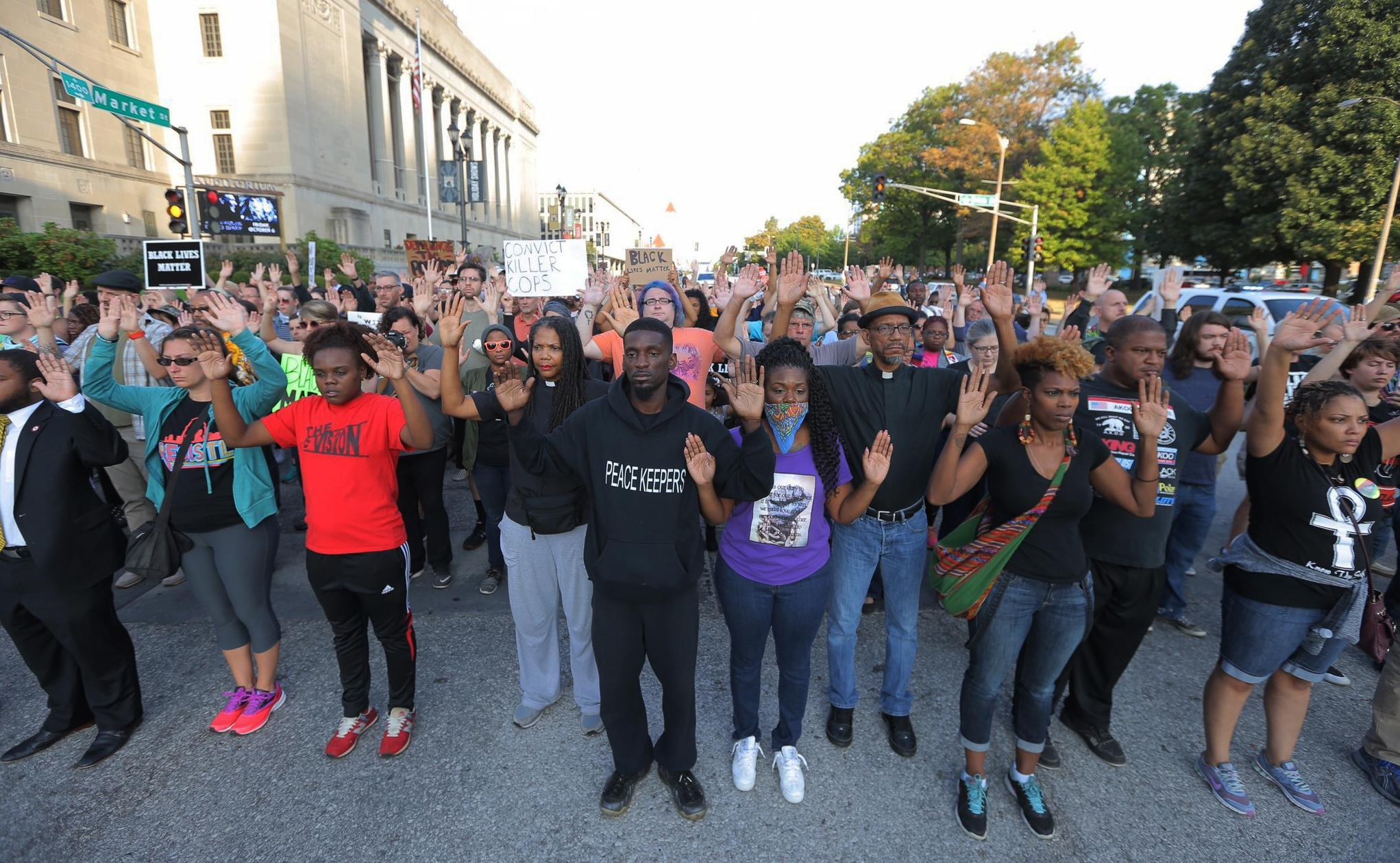 Protesters march in silence down Market Street in St. Louis on Monday, Sept. 18, 2017, in response to a not guilty verdict in the trial of former St. Louis police officer Jason Stockley. Stockley was acquitted on Friday in the 2011 killing of a black man following a high-speed chase. (Cristina Fletes/St. Louis Post-Dispatch via AP)