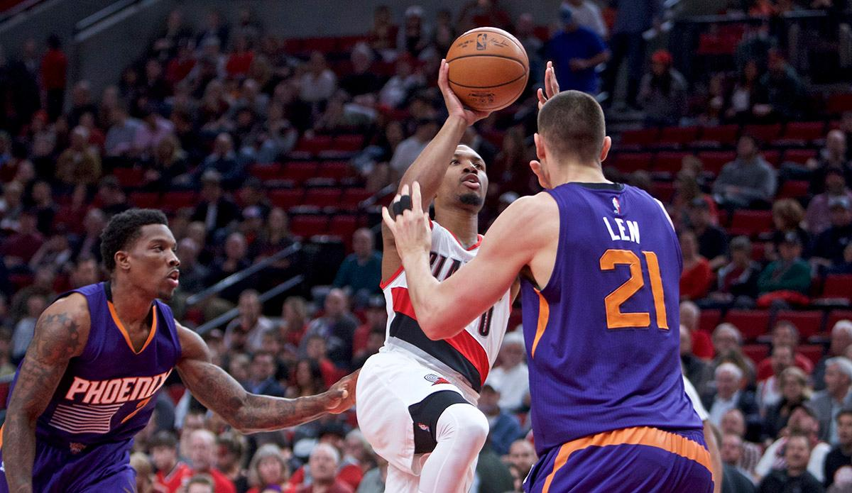 Portland Trail Blazers guard Damian Lillard, center, shoots between Phoenix Suns center Alex Len, right, and guard Eric Bledsoe, left, during the first half of an NBA basketball game in Portland, Ore., Tuesday, Nov. 8, 2016. (AP Photo/Craig Mitchelldyer)