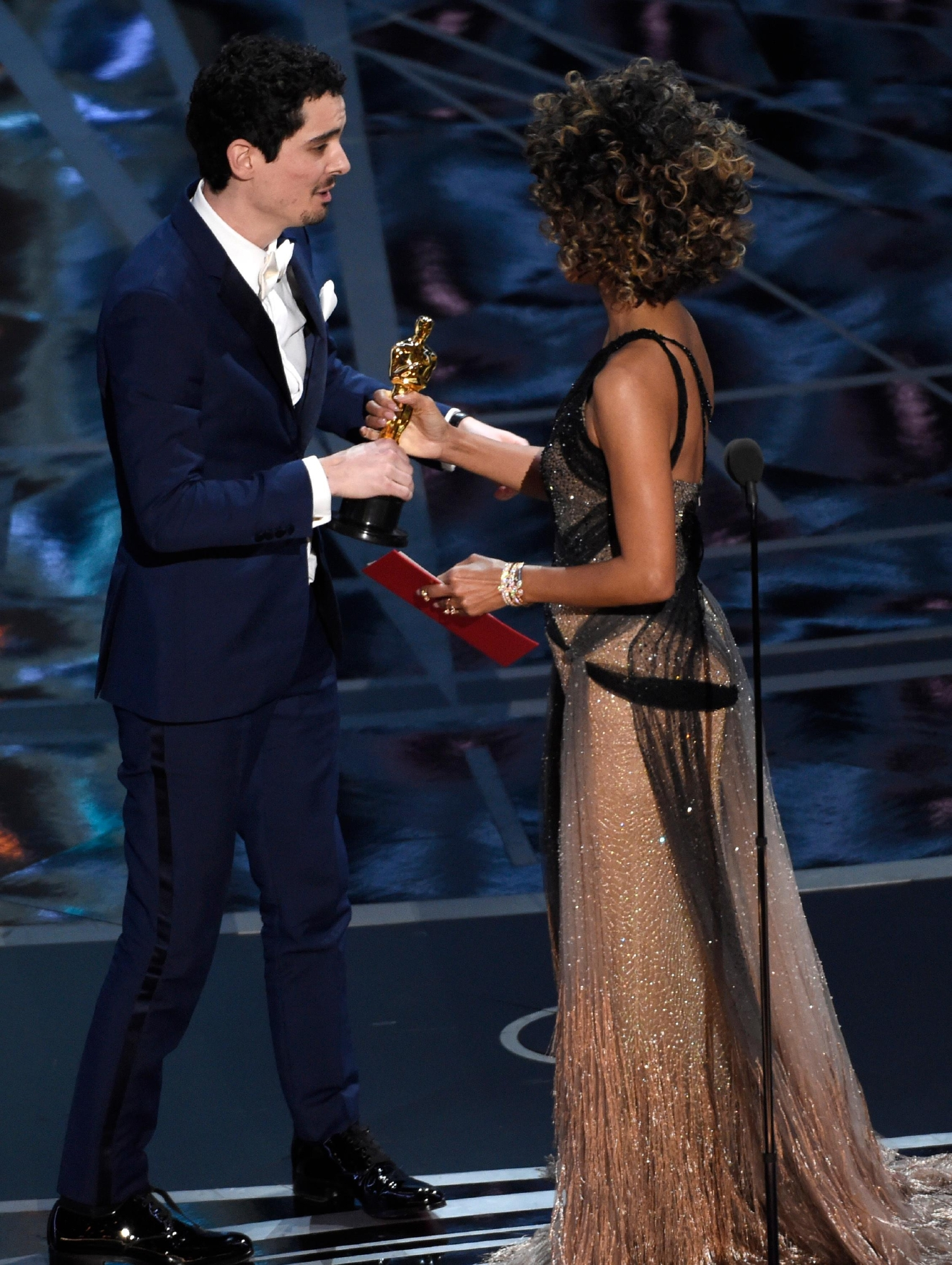"Halle Berry, right, presents Damien Chazelle with the award for best director for ""La La Land"" at the Oscars on Sunday, Feb. 26, 2017, at the Dolby Theatre in Los Angeles. (Photo by Chris Pizzello/Invision/AP)"