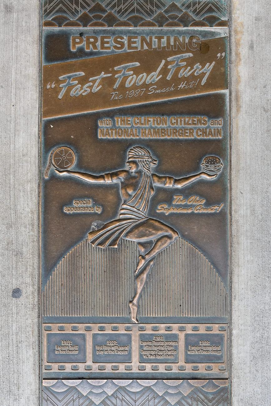 "A humorous plaque outside of the Esquire is embedded in the sidewalk. The design features a faux movie poster that references the story of when the theater almost became a Wendy's. It reads: PRESENTING ""FAST FOOD FURY"" THE 1987 SMASH HIT! WITH THE CLIFTON CITIZENS AND NATIONAL HAMBURGER CHAIN. SPECIAL APPEARANCE BY THE OHIO SUPREME COURT! A timeline of events appears in four frames of 35mm film beneath it. / Image: Phil Armstrong, Cincinnati Refined // Published: 3.17.19"