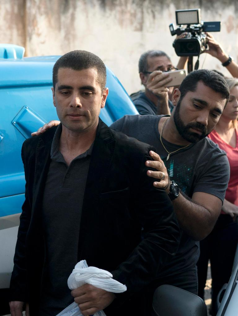"Brazilian ""celebrity"" surgeon Dr. Denis Cesar Barros Furtado is escorted by police after his arrest in Rio de Janeiro, Brazil, Thursday, July 19, 2018. The 45-year-old buttocks enlargement specialist, also known as Dr. ""Bumbum"" or Dr. Fanny, fled when one of his female patients died after a surgical procedure conducted in his apartment. (AP Photo/Leo Correa)"