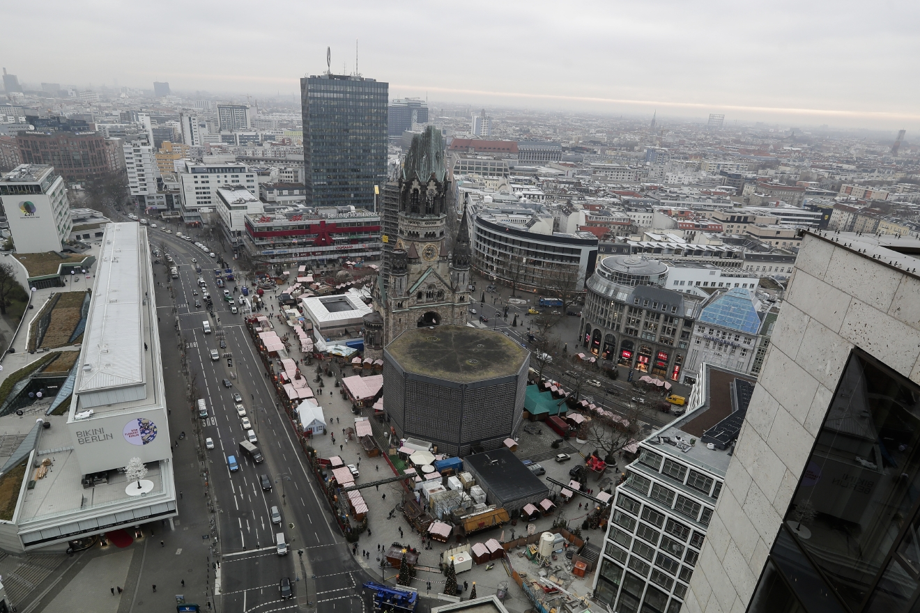 People walk over the re-opened Christmas market, three days after a truck ran into the crowd and killed several people, at the Kaiser Wilhelm Memorial Church in Berlin, Thursday, Dec. 22, 2016. (AP Photo/Markus Schreiber)