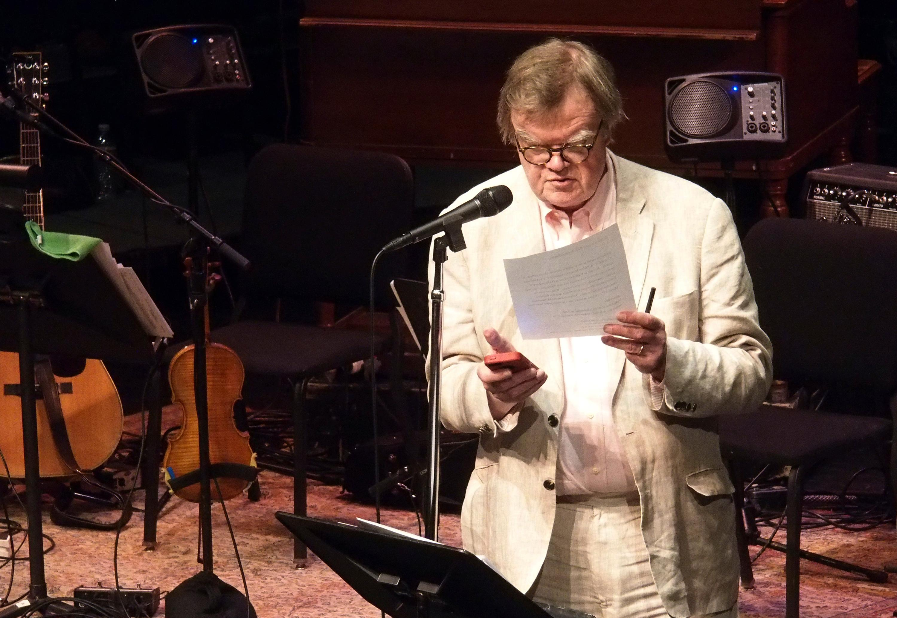 In this Feb. 19, 2016 photo, Garrison Keillor uses his phone at the Fitzgerald Theater in St. Paul to time a promo for an upcoming show. Keillor said Wednesday, Nov. 29, 2017, he has been fired by Minnesota Public Radio over allegations of improper behavior. (Euan Kerr/Minnesota Public Radio via AP)