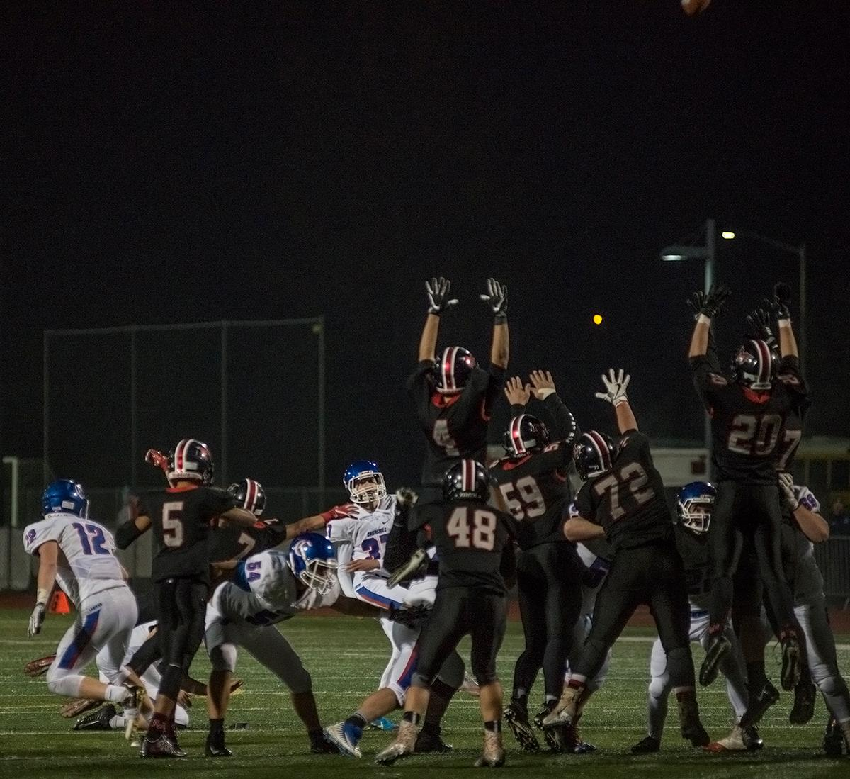 The Mountain View Cougars defense leaps to block a field goal attempt by the Churchill Lancers. The Churchill Lancers defeated the Mountain View Cougars 35-28 on Saturday night at Liberty High School, securing a spot in the 5A state championship. Photo by Abigail Winn, Oregon News Lab