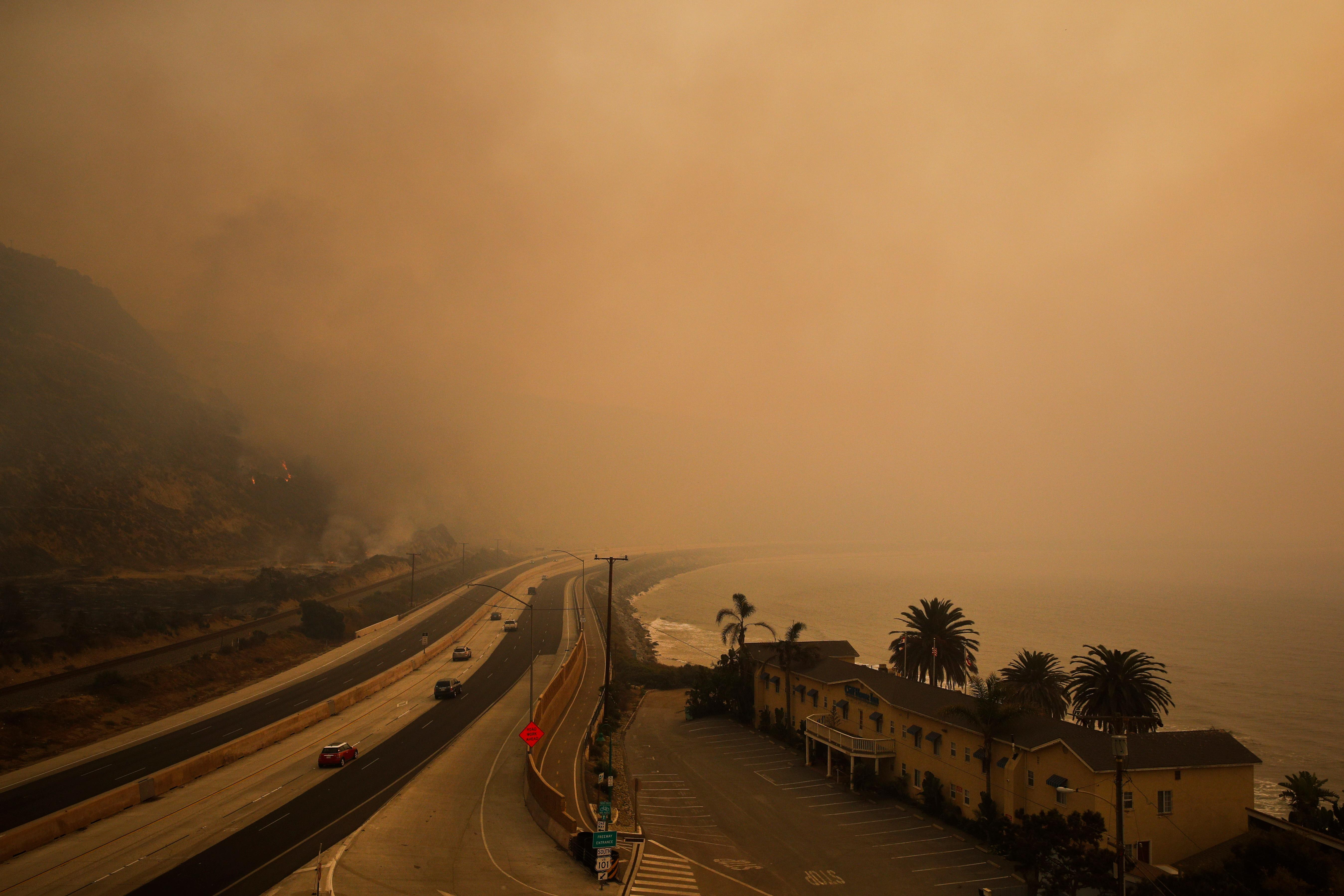 Traffic moves along the 101 Freeway as smoke from a wildfire fills the air in Ventura, Calif., Thursday, Dec. 7, 2017. The wind-swept blazes have forced tens of thousands of evacuations and destroyed dozens of homes. (AP Photo/Jae C. Hong)