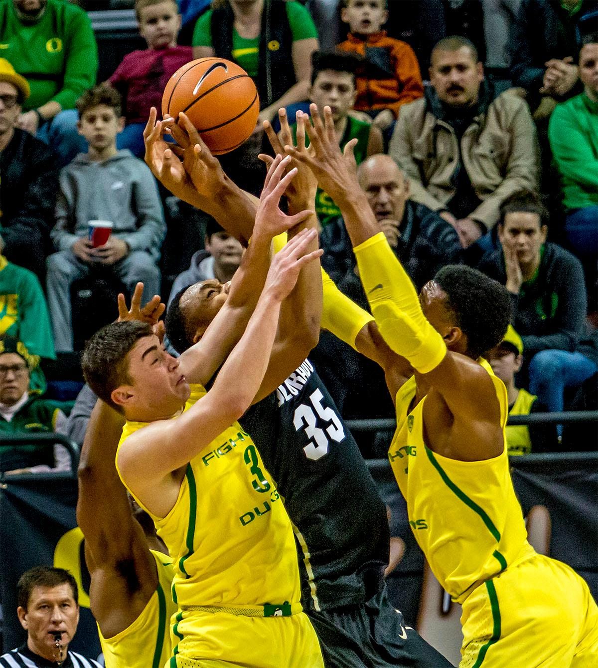 The Duck's fight with the Buffaloes' Dallas Walton (#35) for the rebound. The Oregon Ducks defeated the Colorado Buffaloes 77-62 at Matthew Knight Arena on Sunday. Troy Brown had a season-high score of 21 points, Elijah Brown added 17, while Kenny Wooten and Payton Pritchard added 13 and 12 respectively. Oregon is now 1-1 in conference play. The Ducks next face off against the Oregon State Beavers in Corvallis on Friday, January 5th. Photo by August Frank, Oregon News Lab
