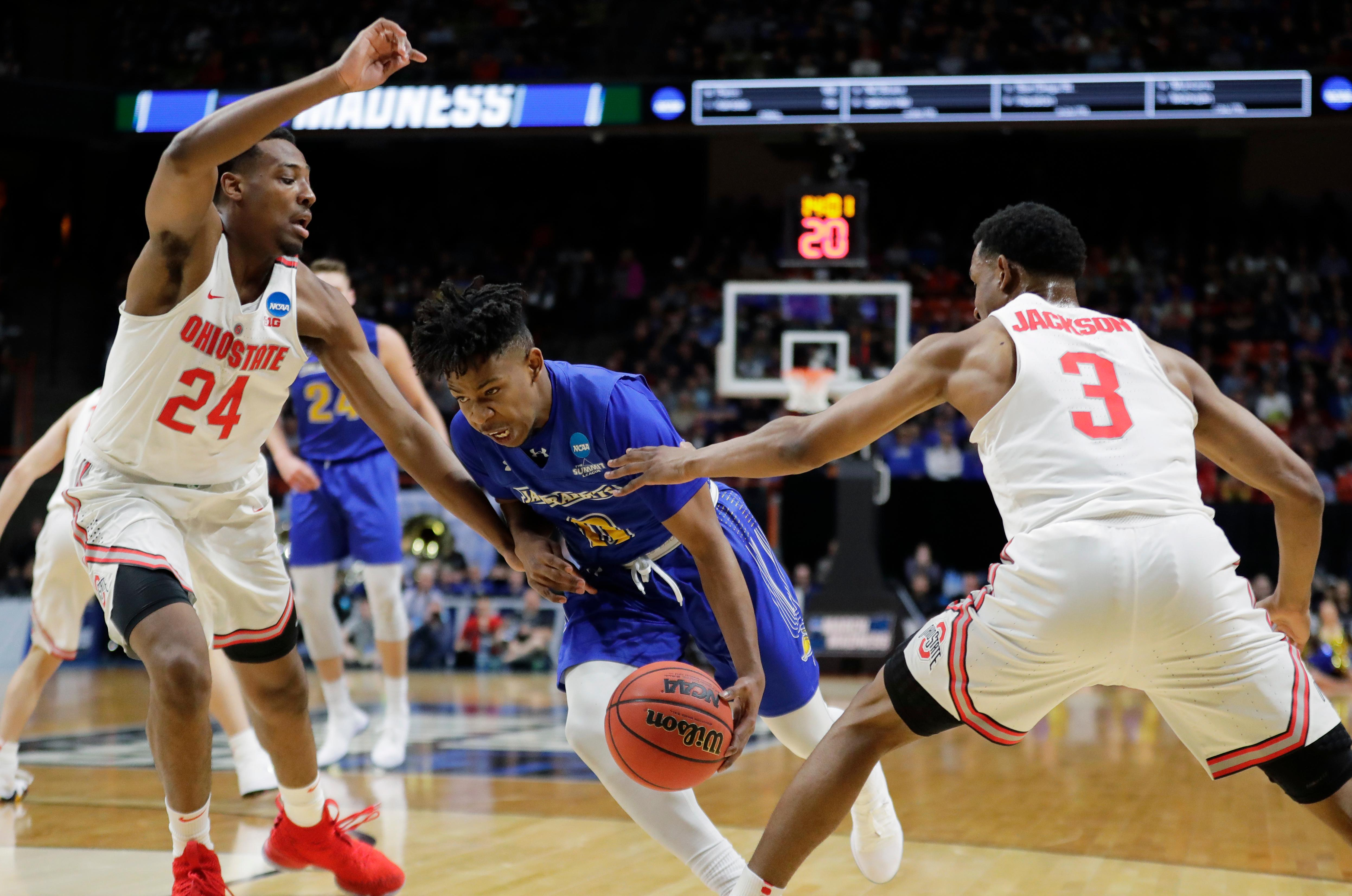 South Dakota State guard Brandon Key, center, drives to the hoop between Ohio State forward Andre Wesson (24) and guard C.J. Jackson (3) during the first half of a first-round game in the NCAA college basketball tournament, Thursday, March 15, 2018, in Boise, Idaho. (AP Photo/Ted S. Warren)