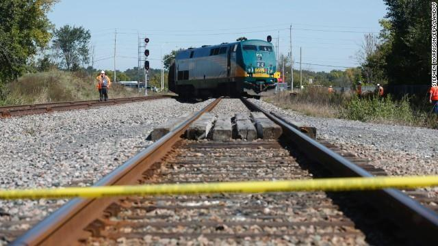 The train sits derailed as officials work at the scene on September 18.