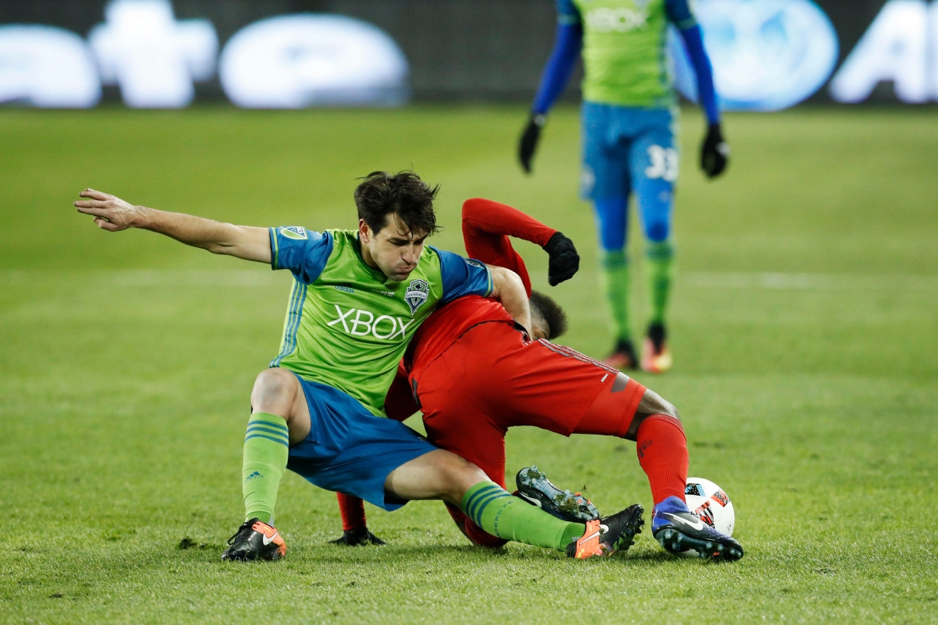 Seattle Sounders midfielder Nicolas Lodeiro, left, and Toronto FC midfielder Armando Cooper battle for a ball during first-half MLS Cup final soccer action in Toronto, Saturday, Dec. 10, 2016. (Mark Blinch/The Canadian Press via AP)