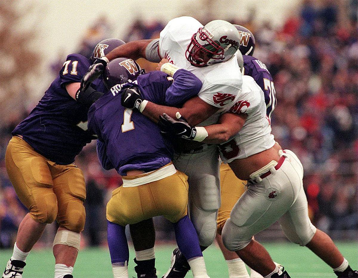 FILE - In this Nov. 22, 1997, file photo, Washington quarterback Brock Huard is sacked by Washington State defenders Gary Holmes and Shane Doyle during an NCAA college football game. Twenty years ago, the senior-laden upstart team from Washington State erased 67 years of hardship with one magical season that ended with the school's first Rose Bowl berth since before World War II. The clincher came on a dreary November day in Seattle that concluded with those in crimson and gray storming the turf of Husky Stadium and celebrating an Apple Cup victory over the Huskies. (Steve Ringman/The Seattle Times via AP, File)