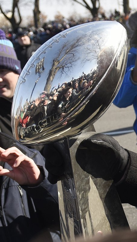 <p>Philadelphia Eagles NFL football head coach Doug Pederson carries the Lombardi Trophy past fans along the parade route during the Super Bowl LII victory parade, Thursday, Feb 8, 2018, in Philadelphia. (AP Photo/Michael Perez)</p>