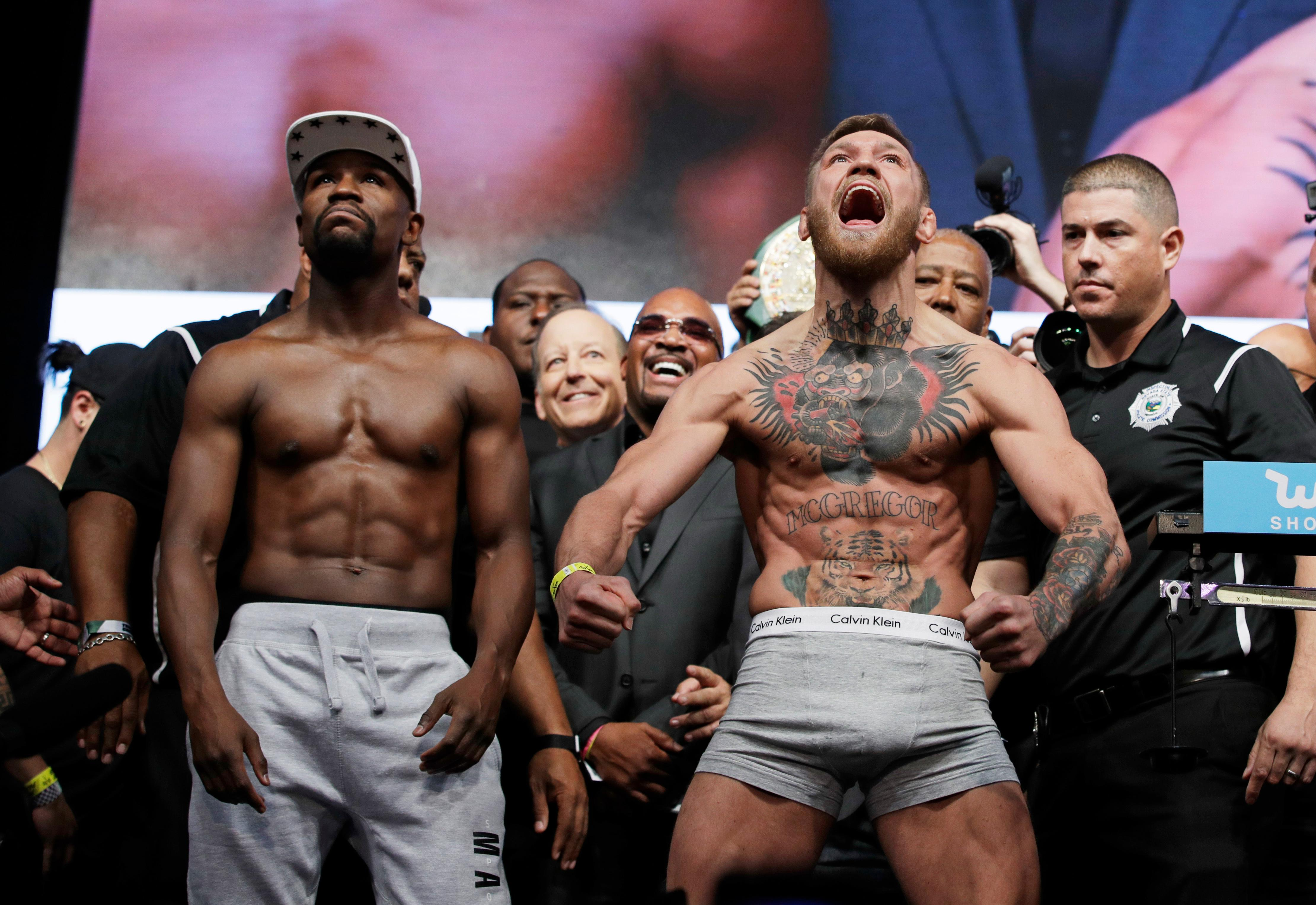 Floyd Mayweather Jr., left, and Conor McGregor pose during weigh-ins Friday, Aug. 25, 2017, in Las Vegas for their Saturday boxing bout. (AP Photo/John Locher)