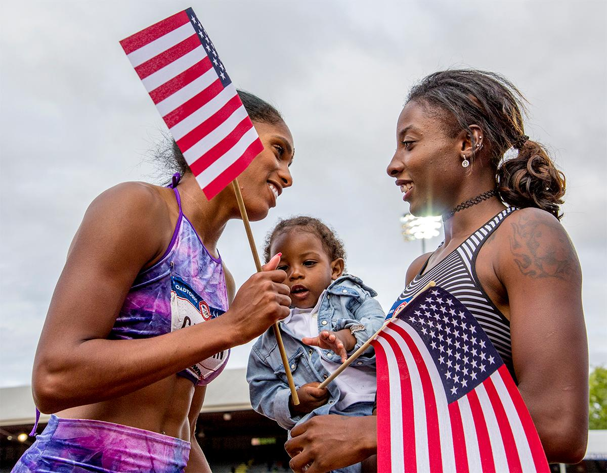 Nia Ali (right) talks with Kristi Castlin as Ali's baby, Titus, decides he want Castlin's flag too. Photo by August Frank, Oregon News Lab