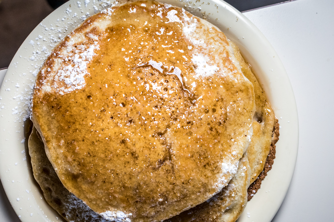 A Couple More: four fluffy pancakes with syrup and powdered sugar / Image: Catherine Viox // Published: 2.1.21