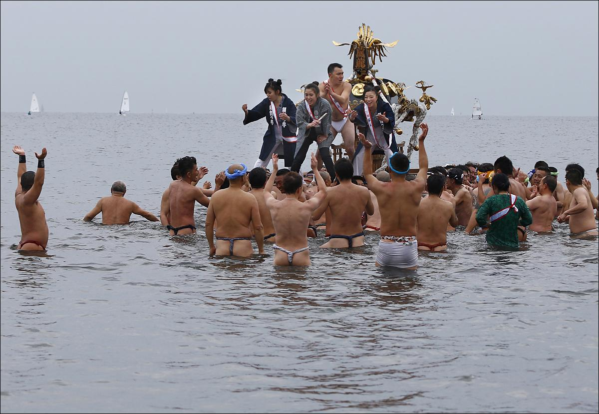 Participants cheer on a portable shrine carried by others as they parade through the sea during a mid-winter festival at Enoshima beach in Fujisawa, west of Tokyo, Sunday, Jan. 17, 2016. The annual festival is held to celebrate youths coming of age this year as well as to pray for the safety of the portable shrines. (AP Photo/Shizuo Kambayashi)