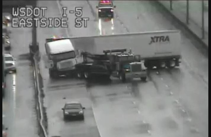 A tow truck works to remove a jackknifed semi in Olympia.  (WSDOT Image)