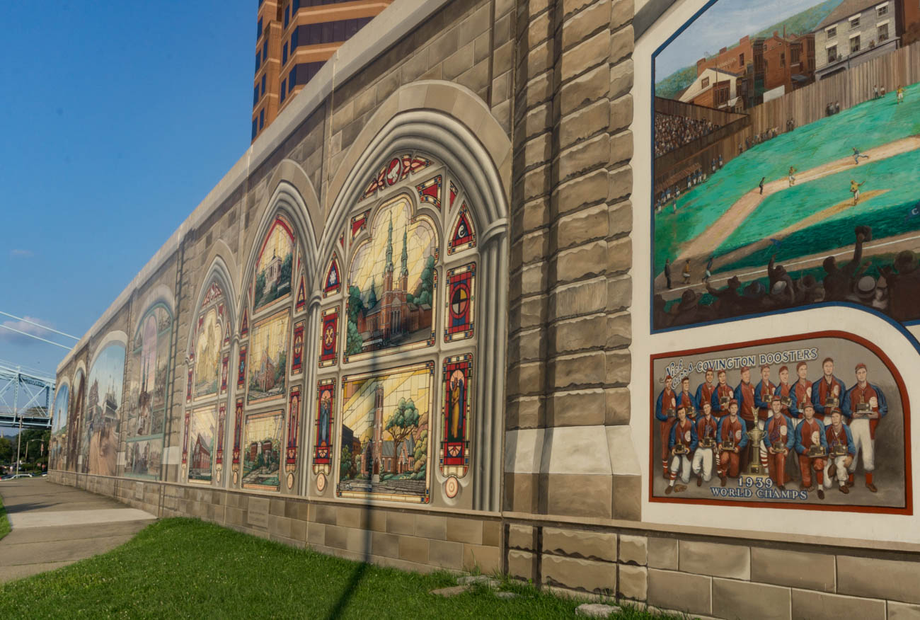 The Roebling Murals are a series of 18 panels spanning the Covington floodwall. The murals depict the rich history of Covington, Kentucky and the Roebling suspension bridge from 8000 BC to present day. The project was started in 2002, completed in 2005, and was done by the group Legacy, headed by artist Robert Dafford. / Image: Sarah Vester // Published: 8.5.17