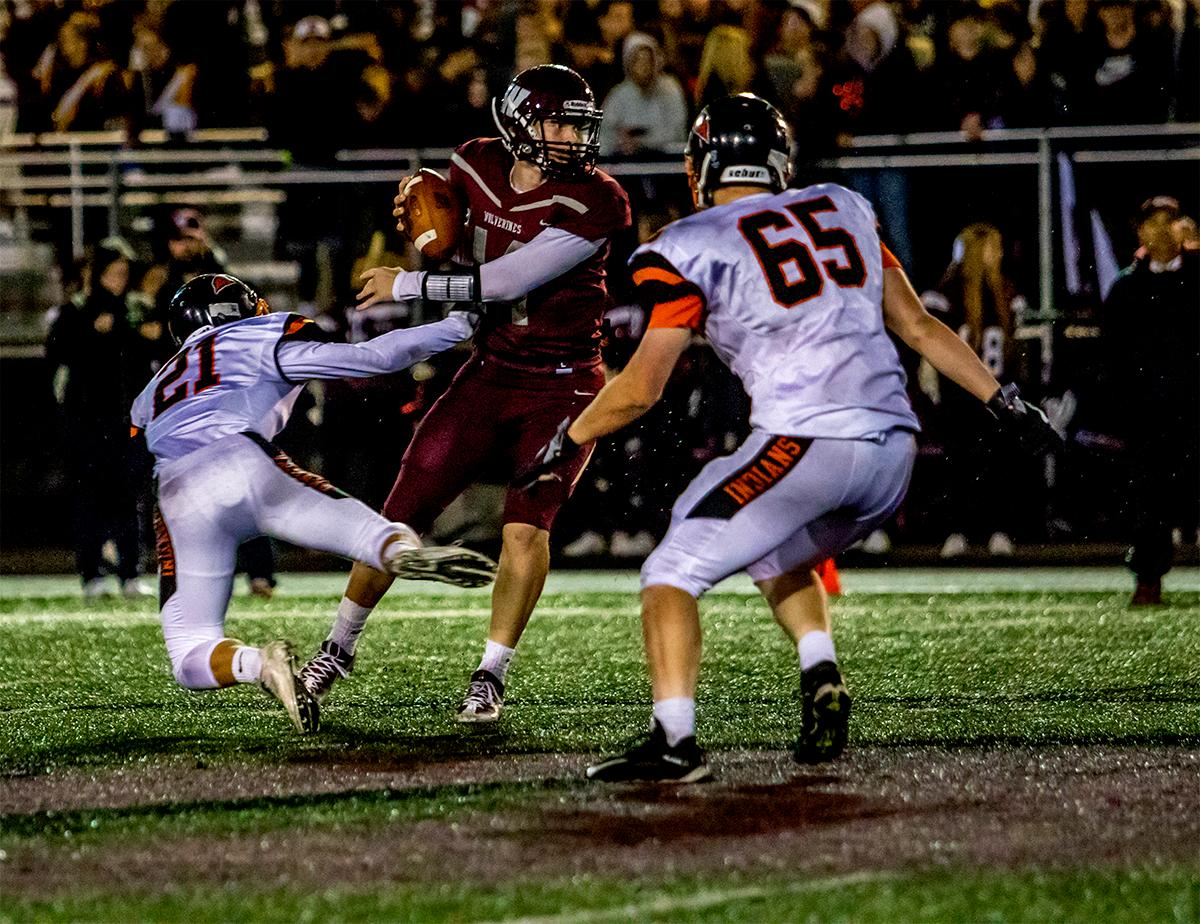 Willamette quarterback Taylor Bridge-Eiler (#14) looks for a teammate to throw too as Roseburg attempts to take him down. The Roseburg Indians defeated the Willamette Wolverines 21-20 at Willamette on Friday. Photo by August Frank, Oregon News Lab
