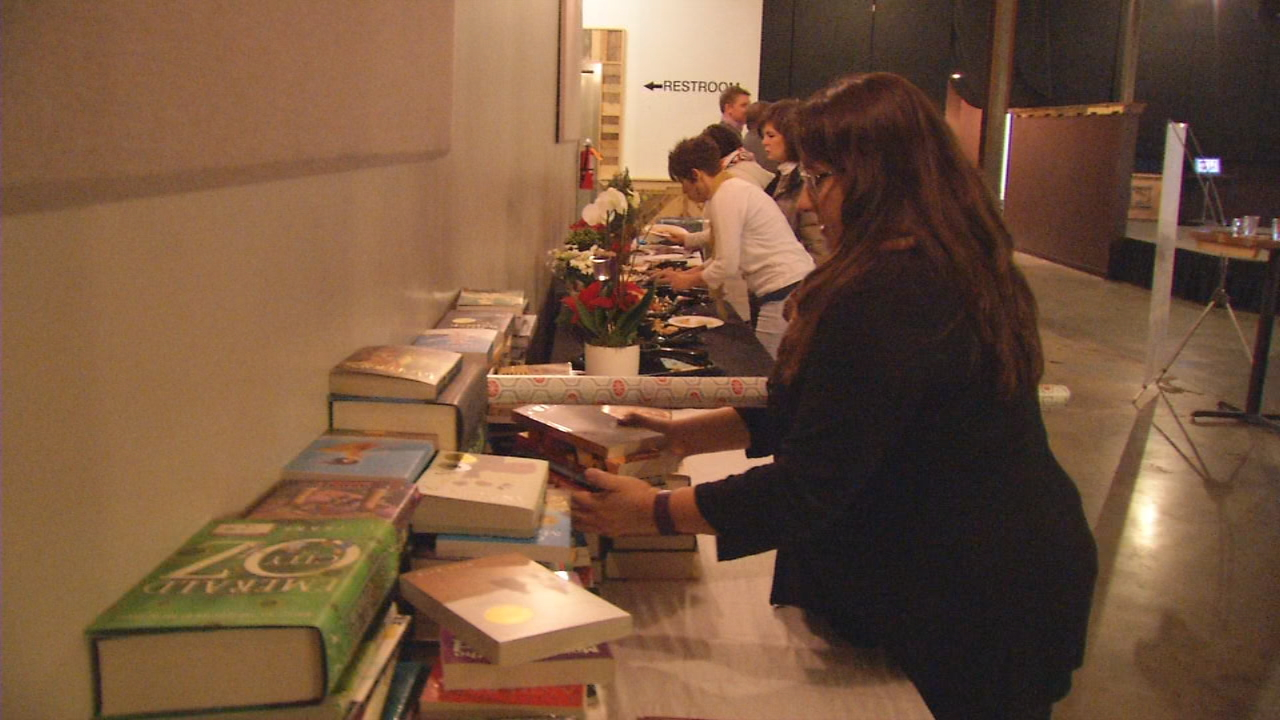 The United Way's Women United gathered Wednesday for its fifth annual holiday book drive wrapping party. (Photo credit: WLOS staff)