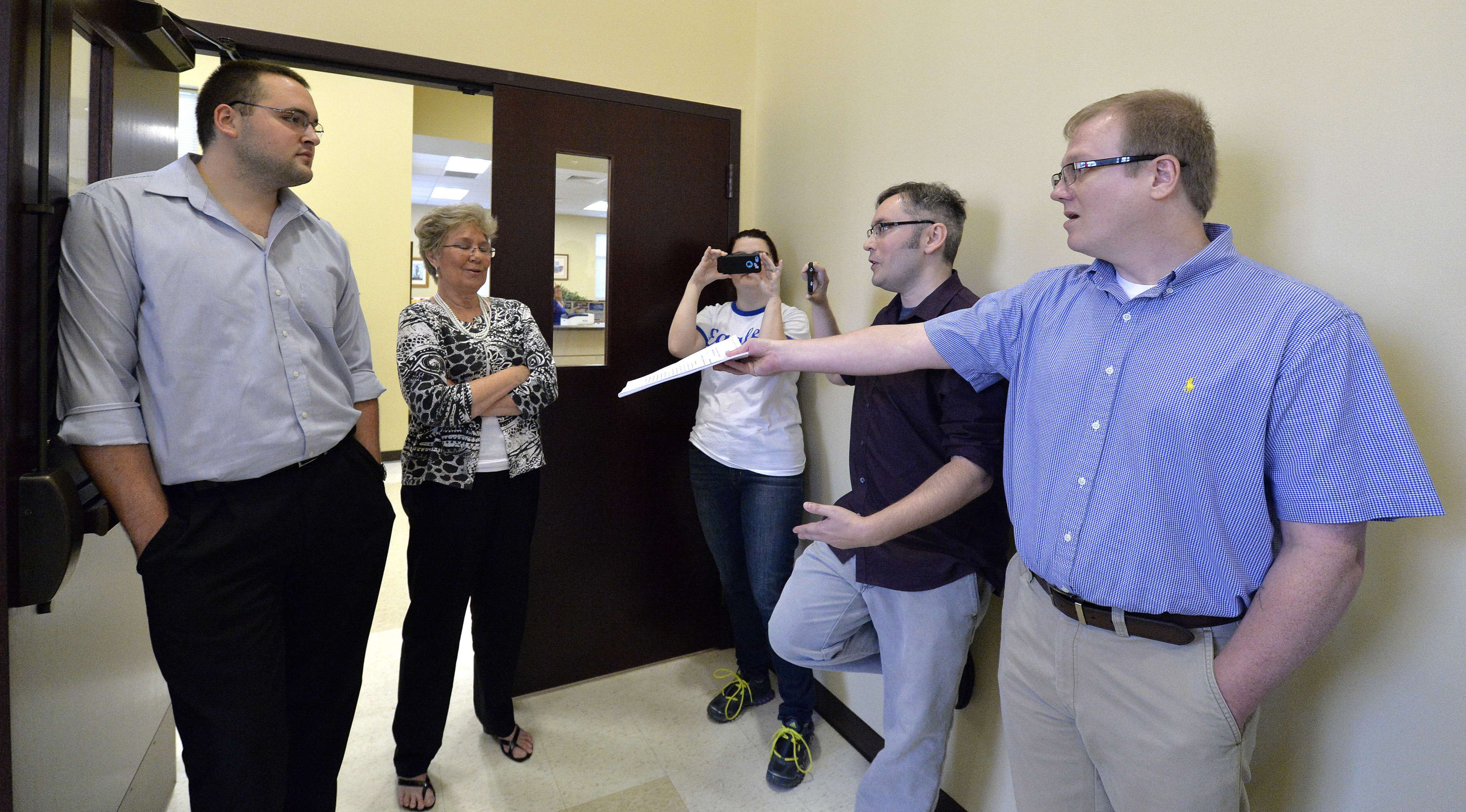 "File - In this Aug. 13, 2015, file photo, David Ermold, right, as he attempts to hand Rowan County clerks Nathan Davis, left, and Roberta Earley, second from left, a copy of the ruling from U.S. District Court Judge David Bunning, instructing the county to start issuing marriage licenses, in Morehead, Ky. Ermold filed to run for county clerk on Wednesday, Dec. 6, 2017, hoping to challenge Kim Davis, who two years ago told him ""God's authority"" prohibited her from complying with a U.S. Supreme Court decision that effectively legalized gay marriage nationwide. (AP Photo/Timothy D. Easley, File)"