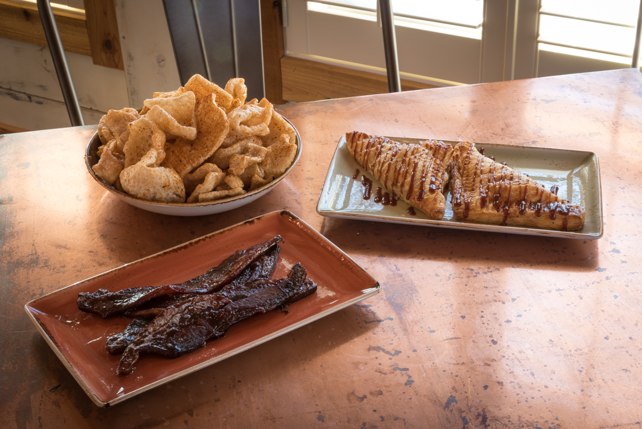 (Background) Pork Rinds, (Foreground, from left) Bacon Sticks, and Pig Newtons / Image: Phil Armstrong, Cincinnati Refined // Published: 2.14.17