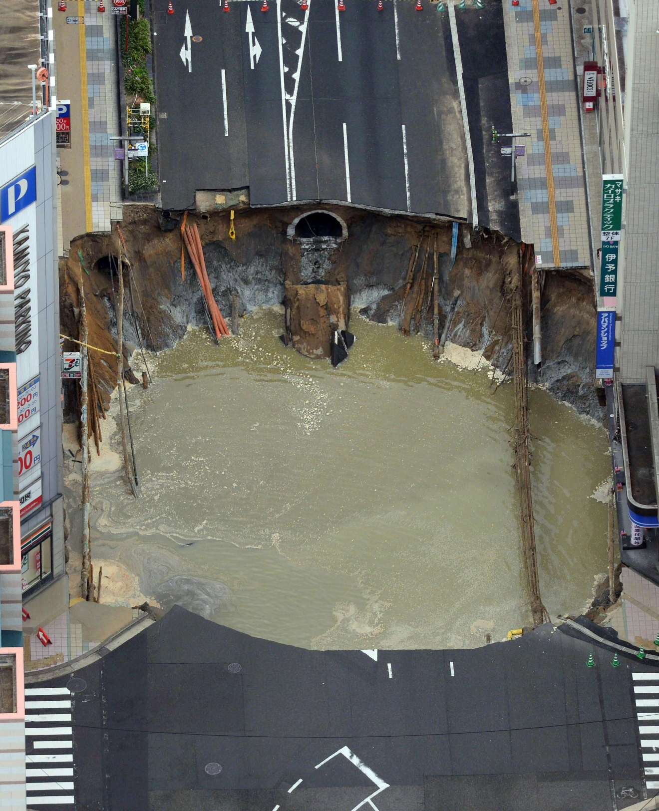 A massive shinkhole is created in the middle of the business district in Fukuoka, southern Japan Tuesday, Nov. 8, 2016. Parts of a main street have collapsed in the city, creating a huge sinkhole and cutting off power, water and gas supplies to parts of the city. Authorities said no injuries were reported from Tuesday's pre-sunrise collapse in downtown Fukuoka. (Kyodo News via AP)