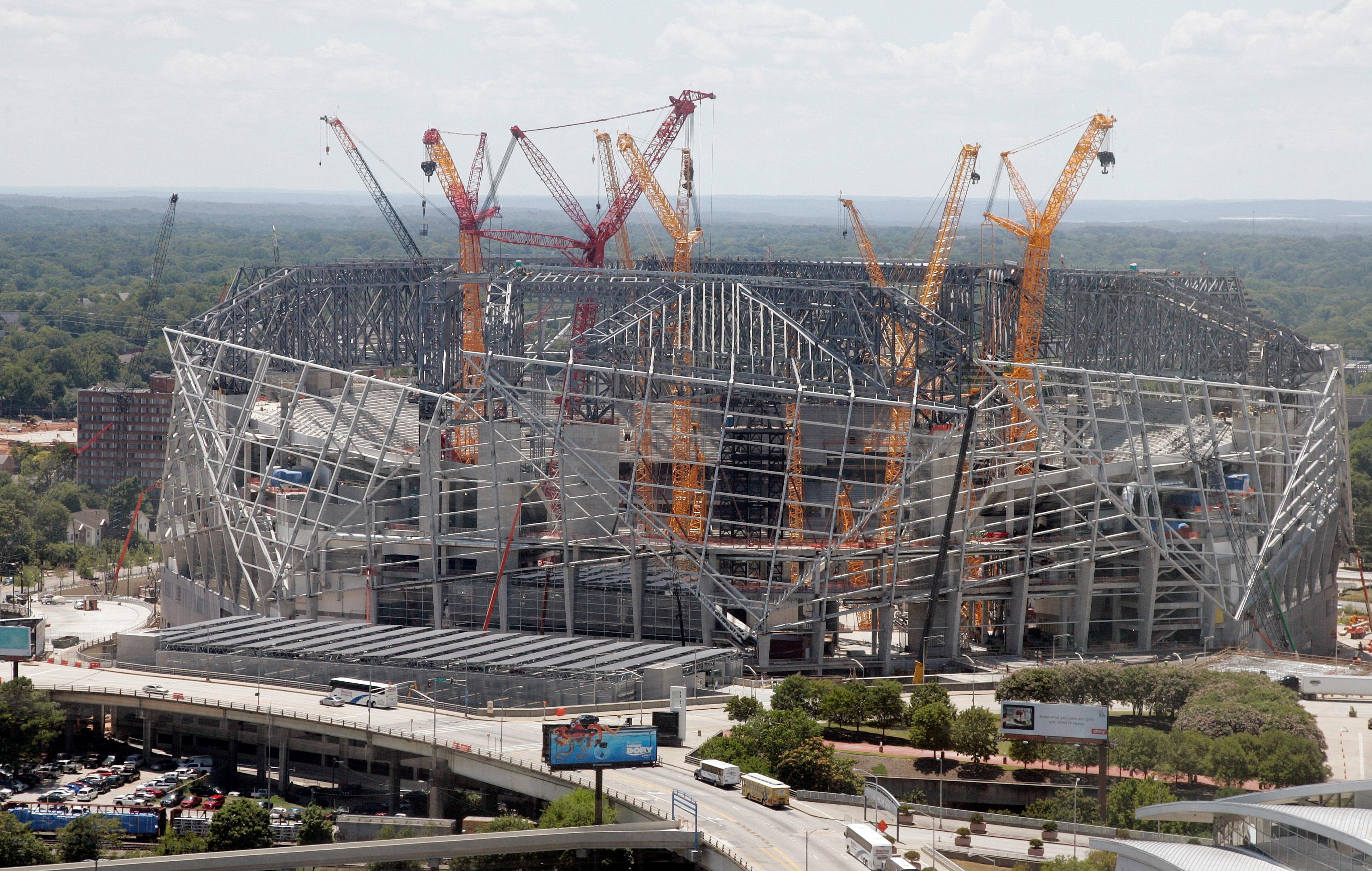 "In this July 14, 2016 photo, construction crews work on the the Mercedes-Benz stadium, in Atlanta. The new $1.5 million stadium is home to the National Football League's Atlanta Falcons and Major League Soccer's Atlanta United. It features a retractable roof; a 1,100-foot ""halo board"" video display; and a giant steel sculpture of a Falcon with its 70-foot wingspan at one of the main entrances. (AP Photo/John Bazemore)"