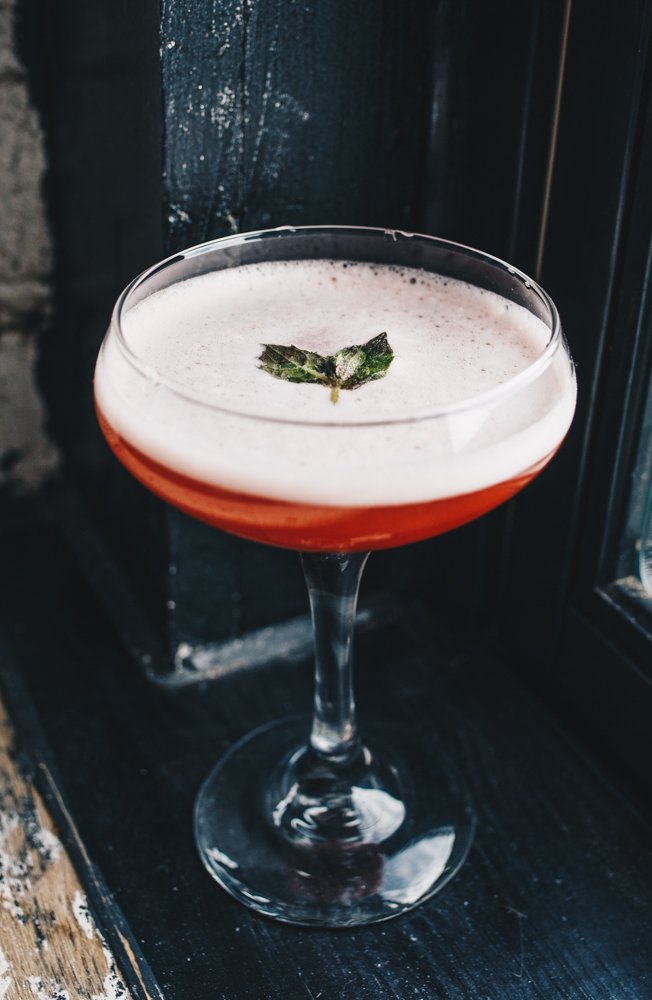 The Southern Belle: bourbon, Campari, pineapple juice, strawberry syrup, and peach bitters garnished with fresh mint / Image: Catherine Viox // Published: 3.24.19