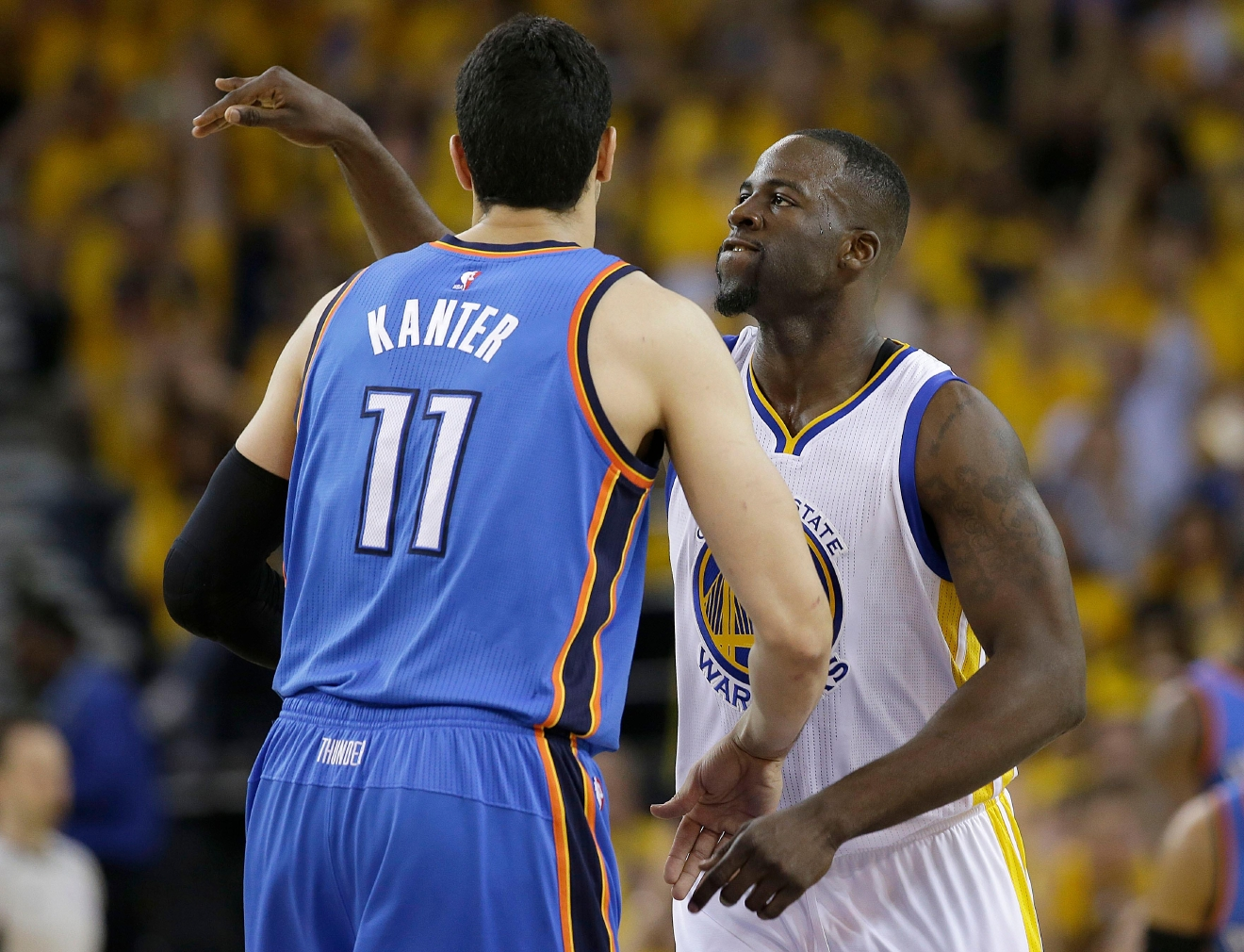 Golden State Warriors forward Draymond Green, right, reacts after scoring by looking at Oklahoma City Thunder center Enes Kanter (11) during the first half of Game 2 of the NBA basketball Western Conference finals in Oakland, Calif., Wednesday, May 18, 2016. (AP Photo/Marcio Jose Sanchez)